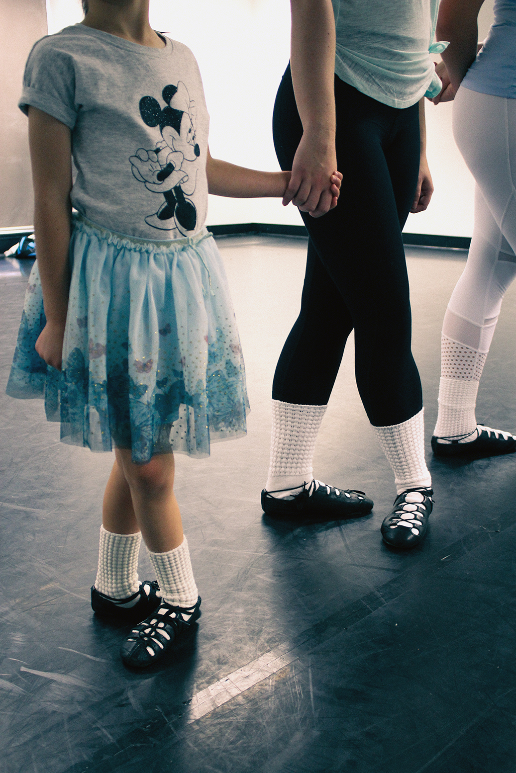 A beginner Irish dancer in soft shoes holds hands with an older girl