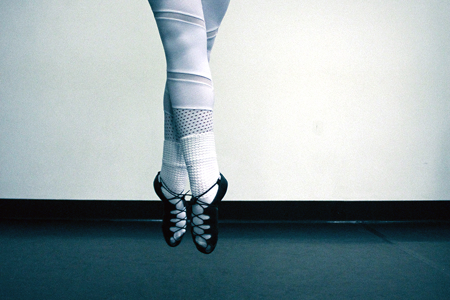 An Irish dancer in soft shoes jumps in the air with pointed toes