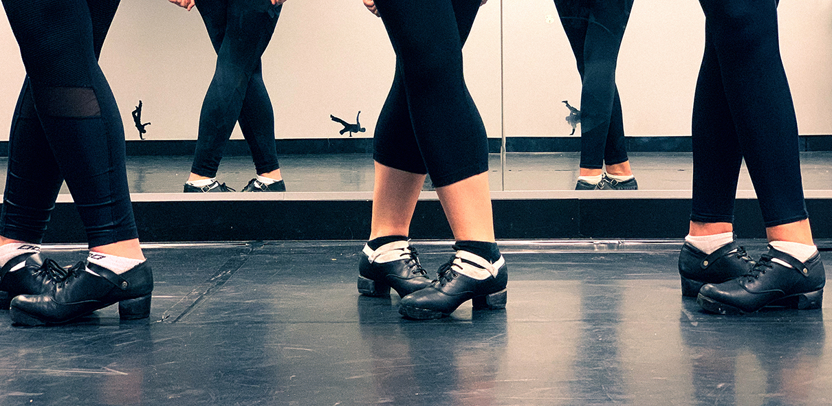 Three Irish dancers in hard shoes stand in fifth position in a studio