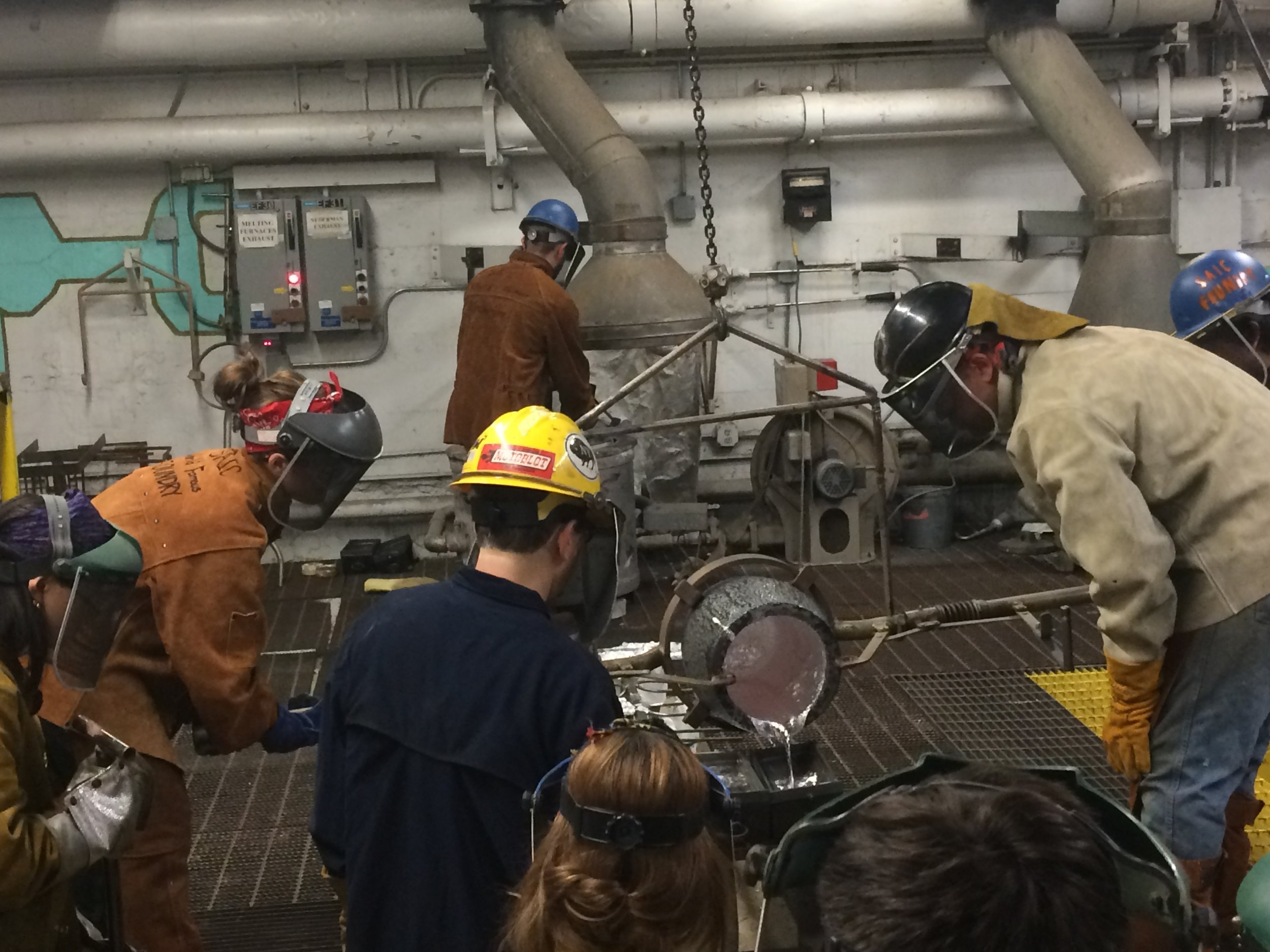Majenta on the left helping lead an aluminum pour.