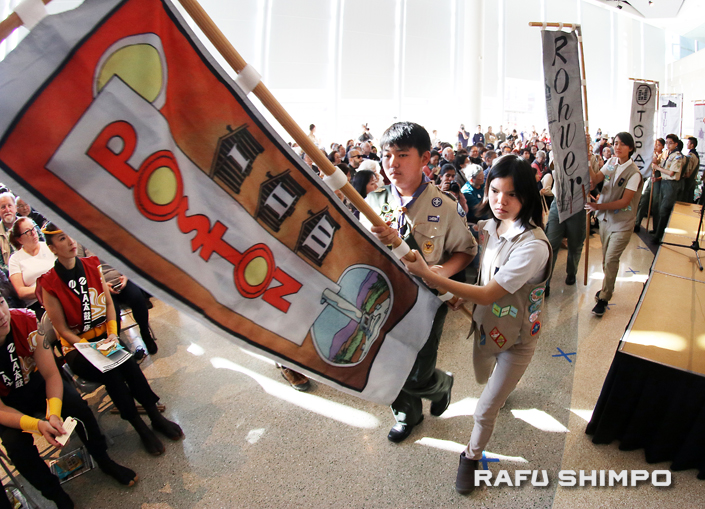 Above and below: Boy Scouts and Girl Scouts carried banners representing the War Relocation Authority and Justice Department camps where Japanese Americans were detained during World War II.