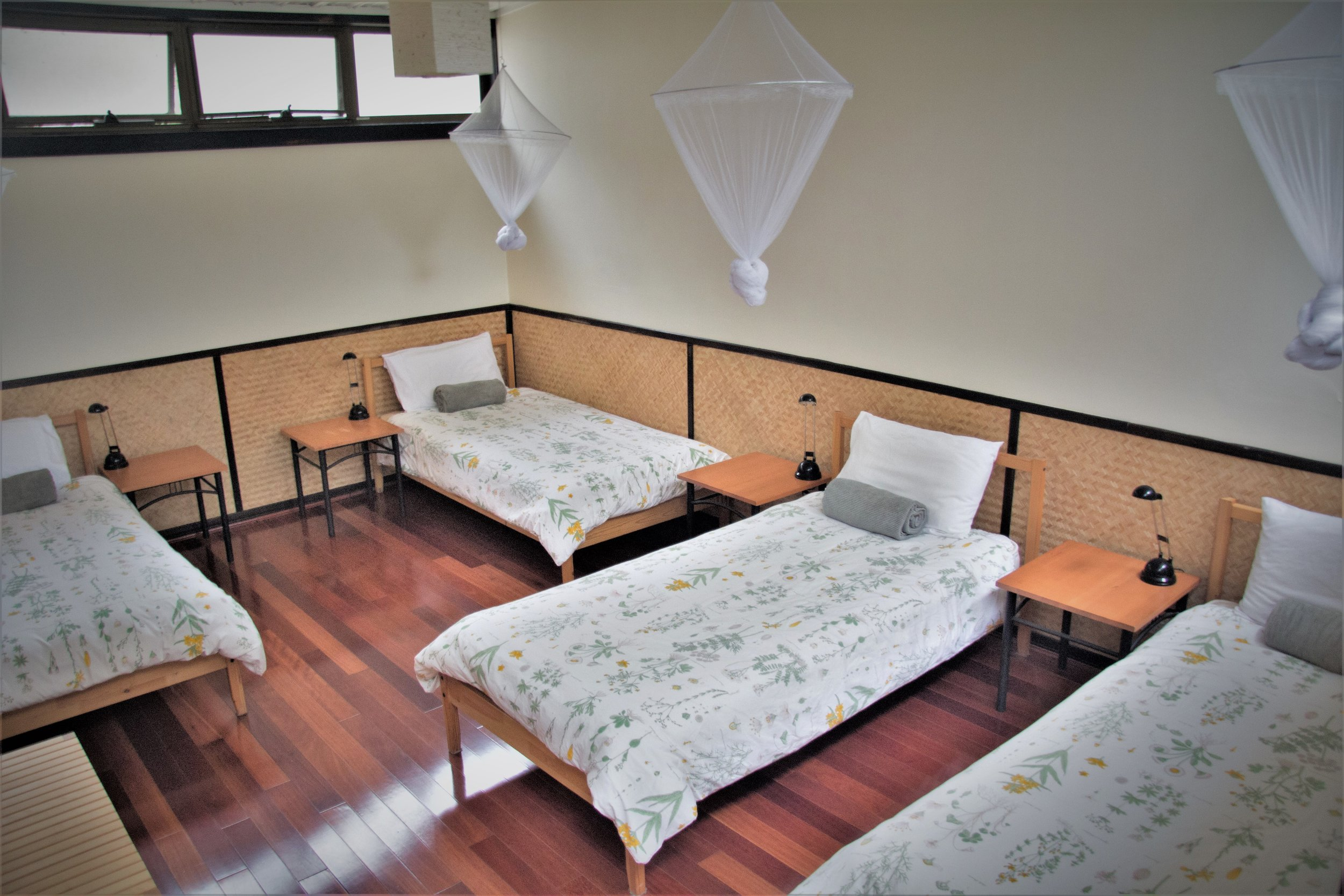 PACKAGE 3 - QUADRUPLE ROOM W/SHARED FACILITIES Features: 4 x Single Beds, communal bathrooms, polished wooden floors, fans + heater, free high speed WiFi, free parking. Access to all yoga classes + 3 vegan meals daily + workshops.
