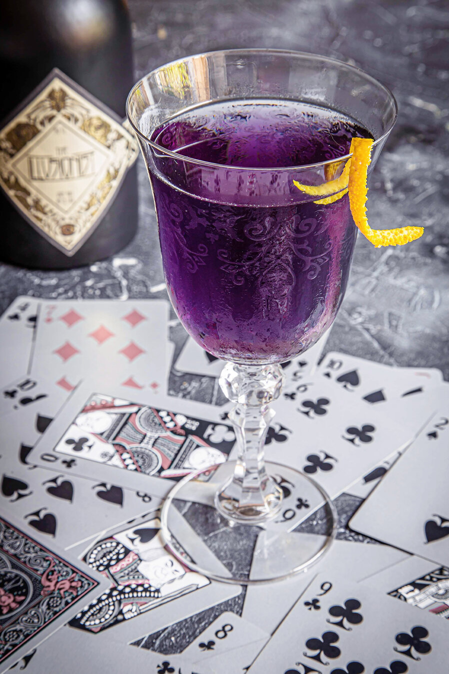 Play your cards - Don't settle for less and master your game with the Illusionist Dry Gin.5cl Illusionist Dry Gin1cl Curaçao1.5cl Raspberry syrupFill with Hibiscus TonicGarnish - Orange Zest