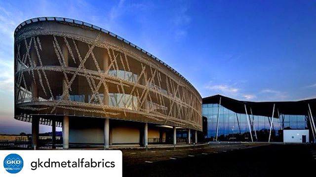 Posted @withrepost • @gkdmetalfabrics The HQ of the National Statistical Office in South Africa provides more than 31,800 square meters office space for 3,500 employees. The glazed rotunda at the main entrance was covered with a visually seamless shell made of metal fabric from GKD. A total of 41 panels of different widths, each measuring 10.14 meters in length, were wrapped around the building to give it the appearance of a drum. In African culture, the drum is considered an invitation to communicative cooperation. The metallic membrane not only makes a key contribution to fulfillment of the Green Building requirements, but also serves as effective solar protection for the fully glazed façade. The fabric reduces solar input into the building, while at the same time significantly reducing the heating up of the façade. This interaction leads to considerably reduced air conditioning costs. At the same time, the woven shell grants employees at the National Statistical Office unrestricted views out of the building thanks to its high degree of transparency. . #gkd #gkdmetalfabric #gkdmetalfabrics #facadefriday #architecture #design #facadefriday #sunshading #solarcontrol #metalmesh #designwithmetal