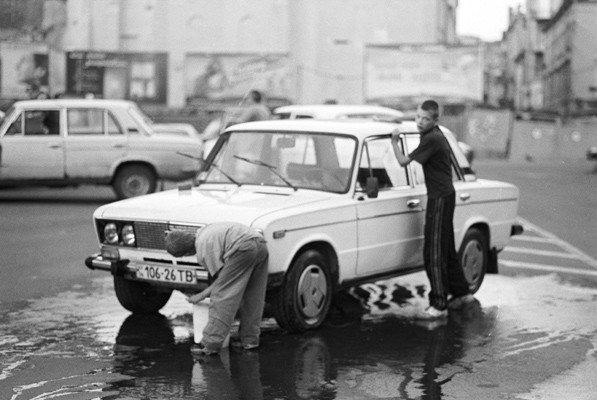 A couple of boys were washing a white Lada in the middle of the street.