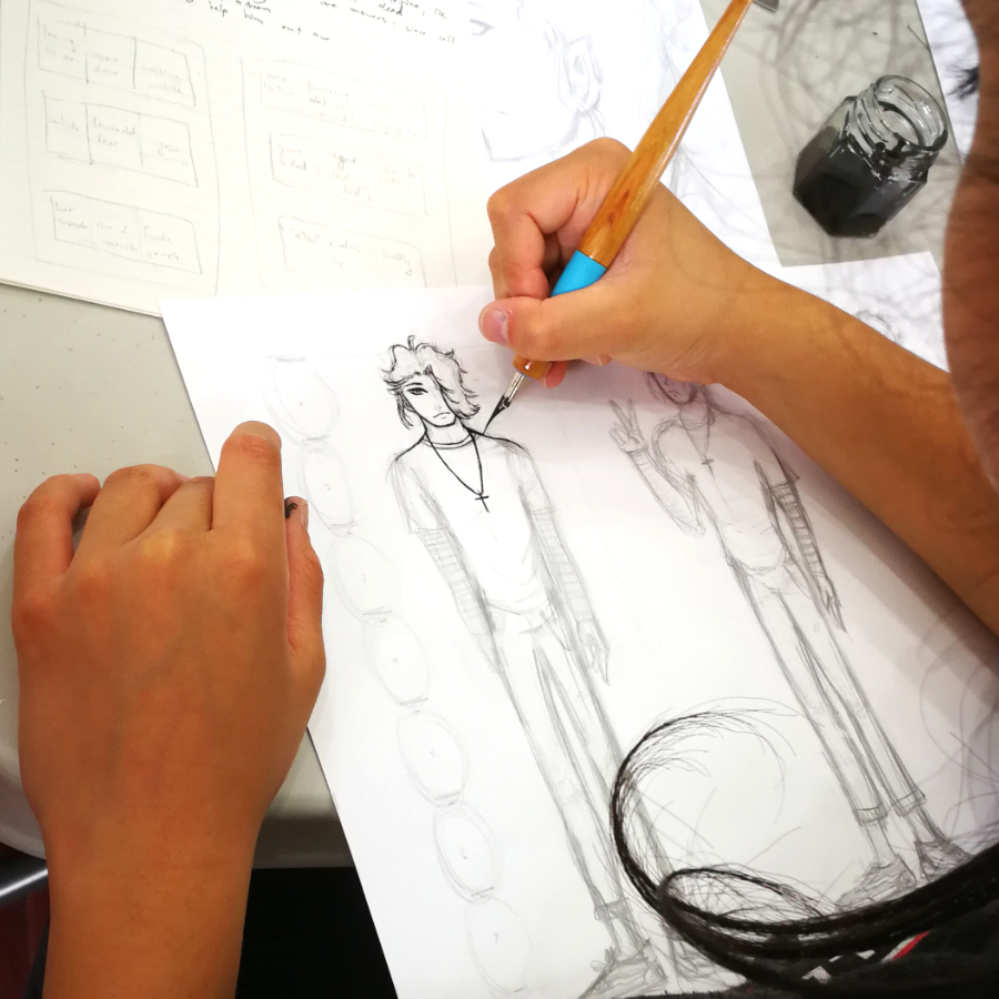 A student inking a character with a nib pen in the manga art summer camp