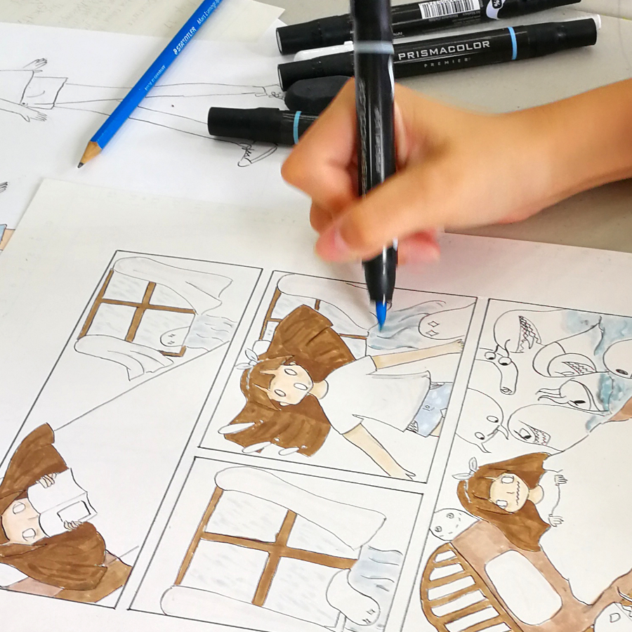 A student colouring a comic page with prismacolor markers in the manga art summer camp