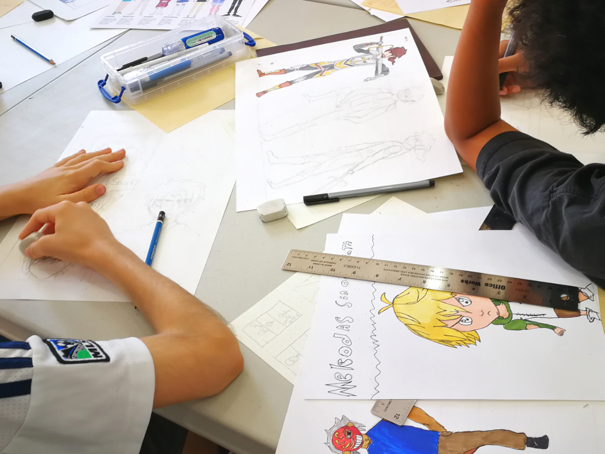 Students working on manga pages, with various anime drawings on the table