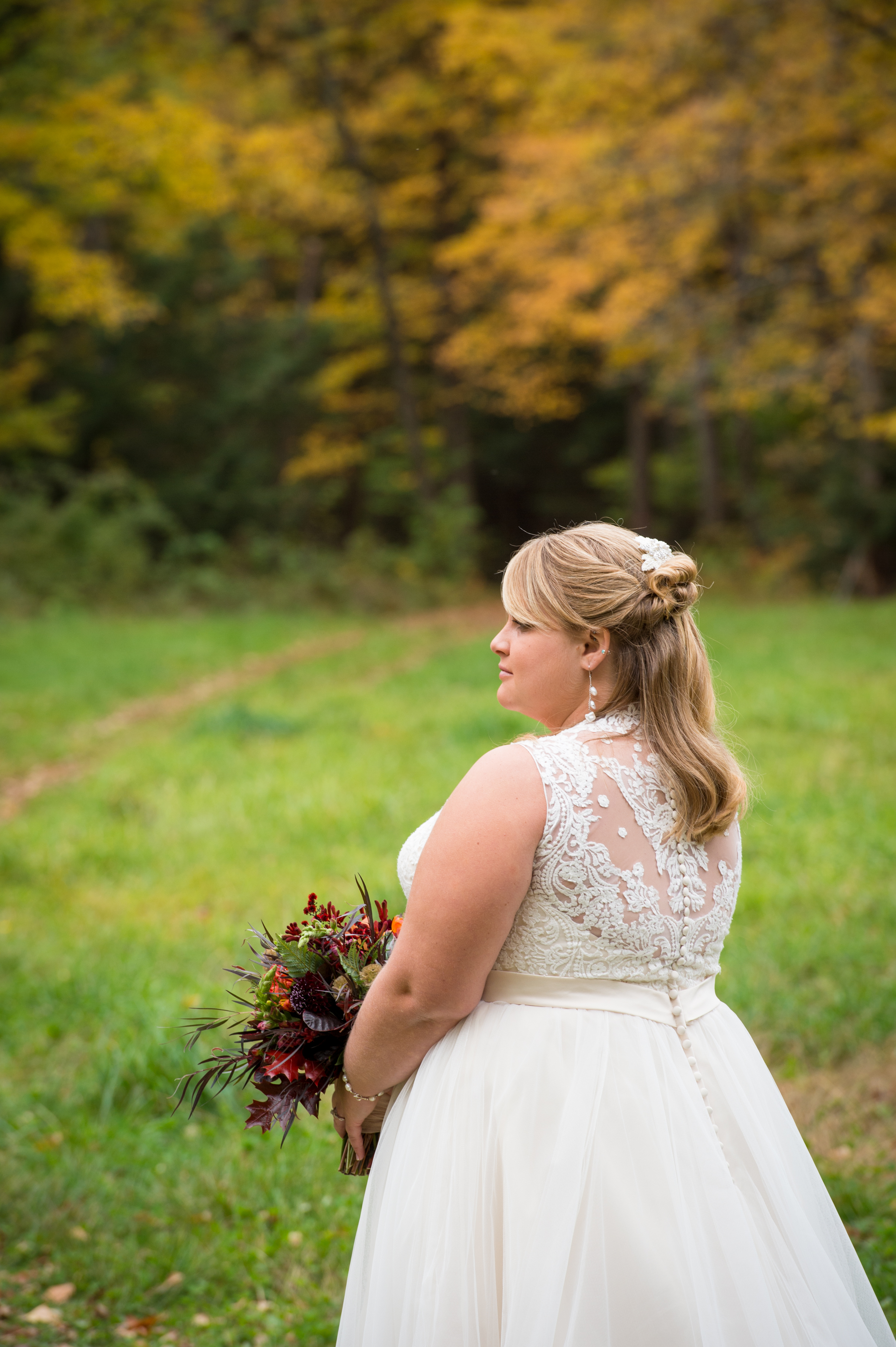 Marrier in wedding dress standing in a field with bouquet during Boston wedding Michelle Schapiro Photography