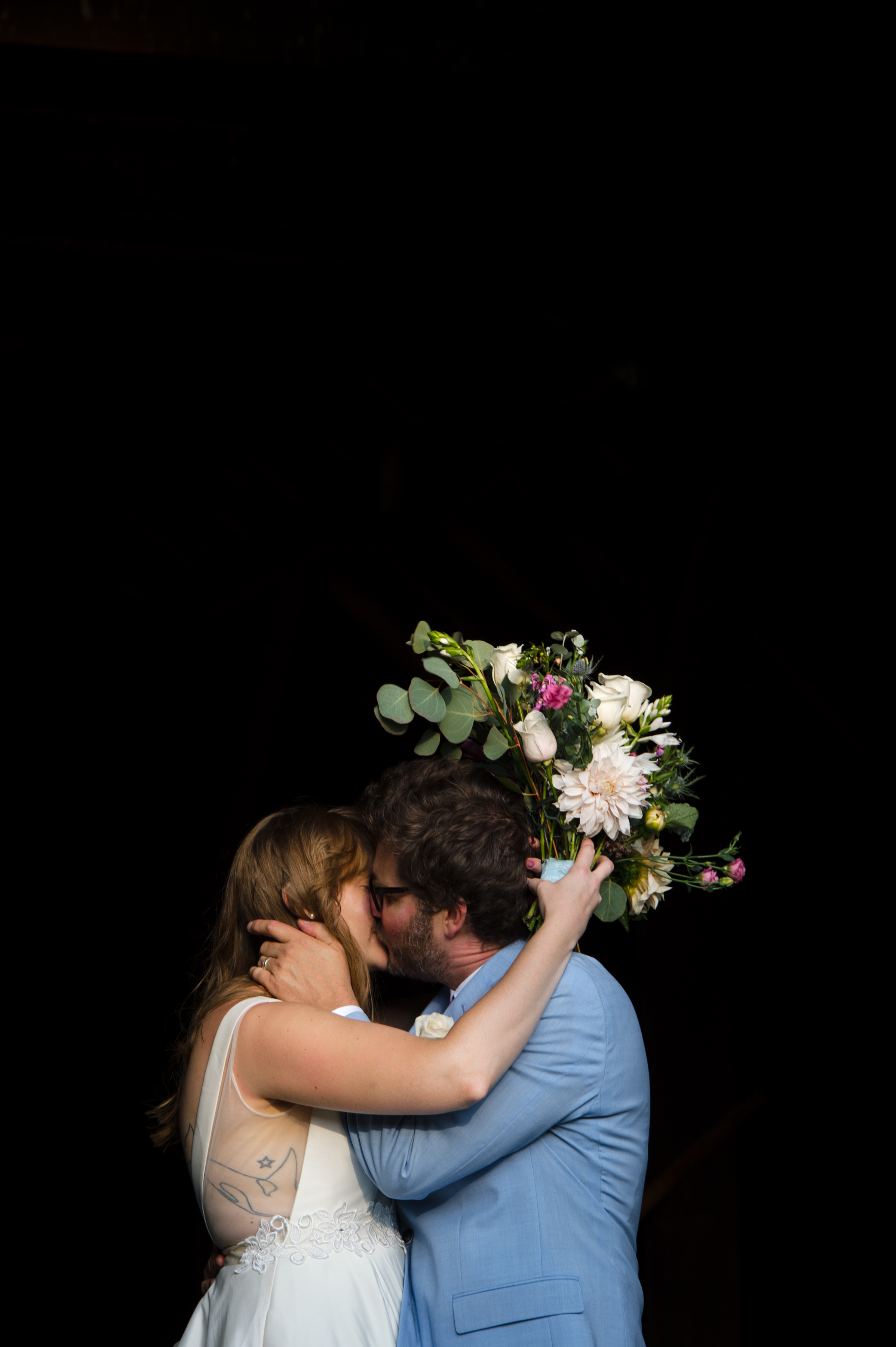 newlywed couple kiss while holding bouquet against black backdrop at Boston wedding Michelle Schapiro Photography
