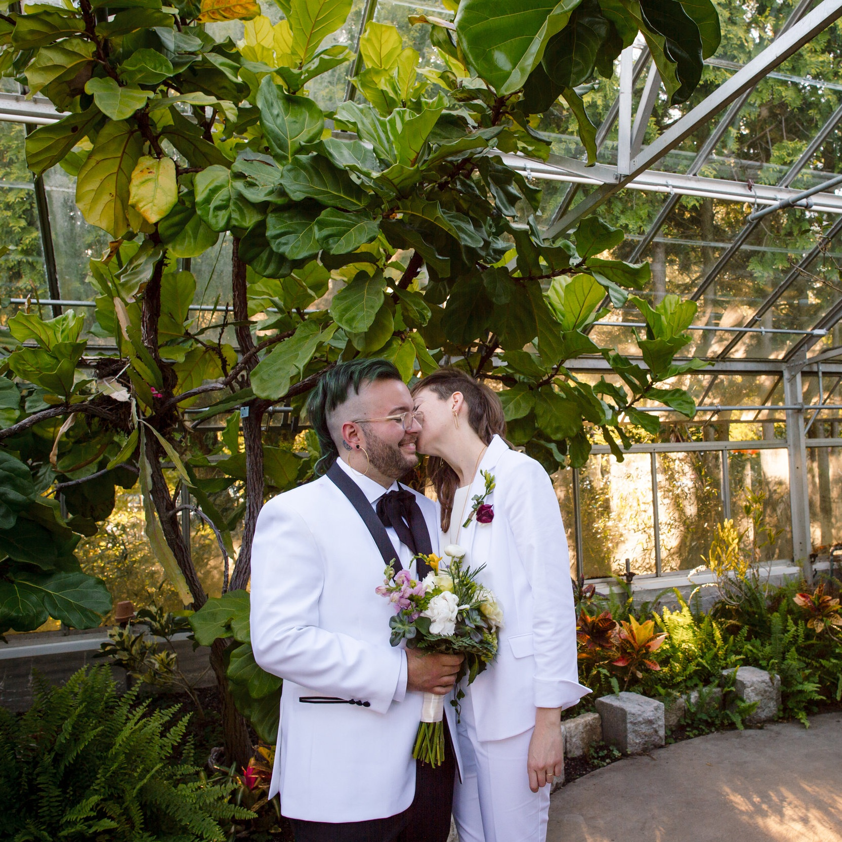 newlywed couple kiss on cheek at Roger Williams Botanical Center in Providence Rhode Island