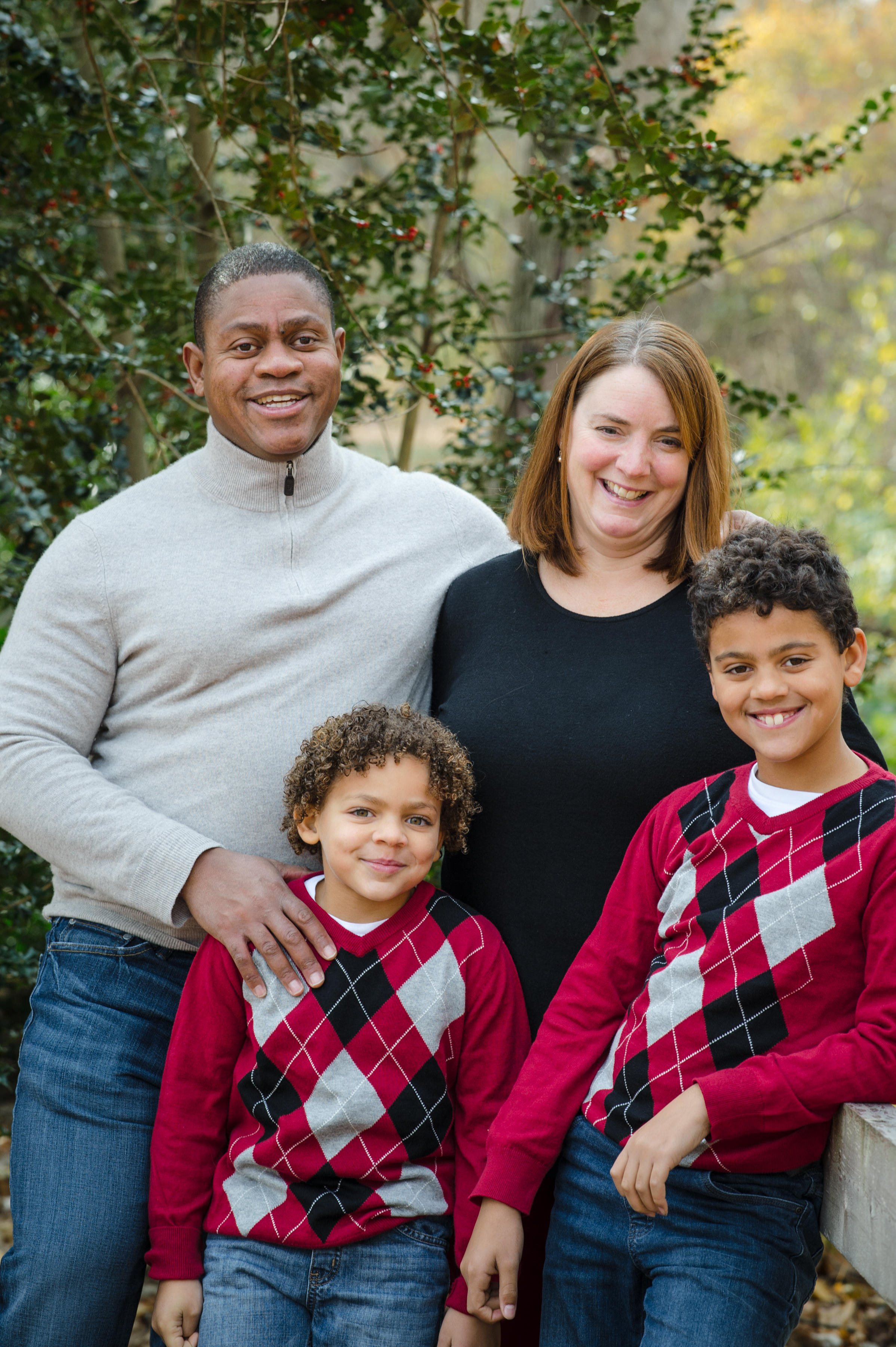 Parents and two children in matching sweaters smile during autumn family photo session in Boston Massachusetts Michelle Schapiro Photography