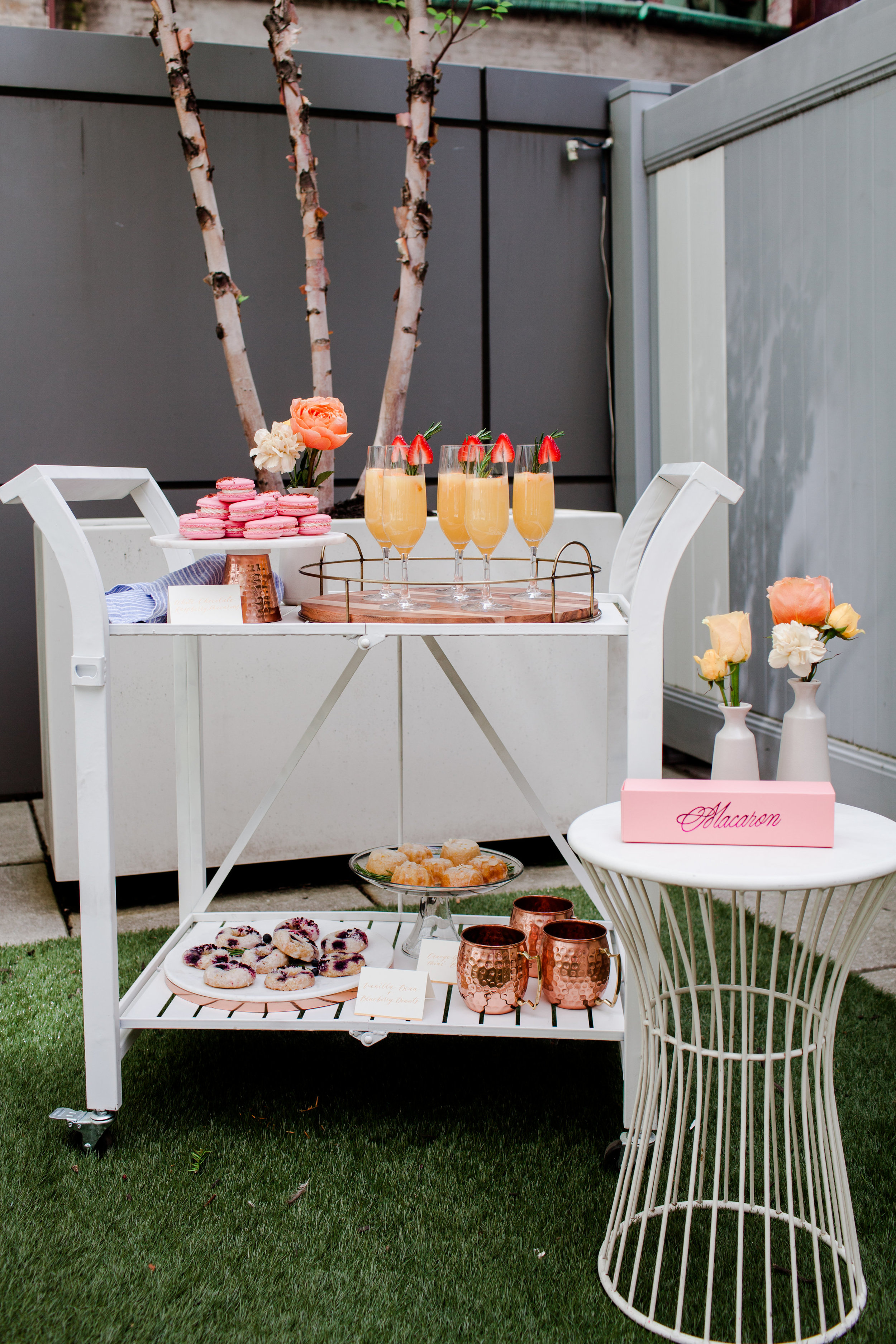 outdoor rooftop brunch decor with bright flowers and desserts