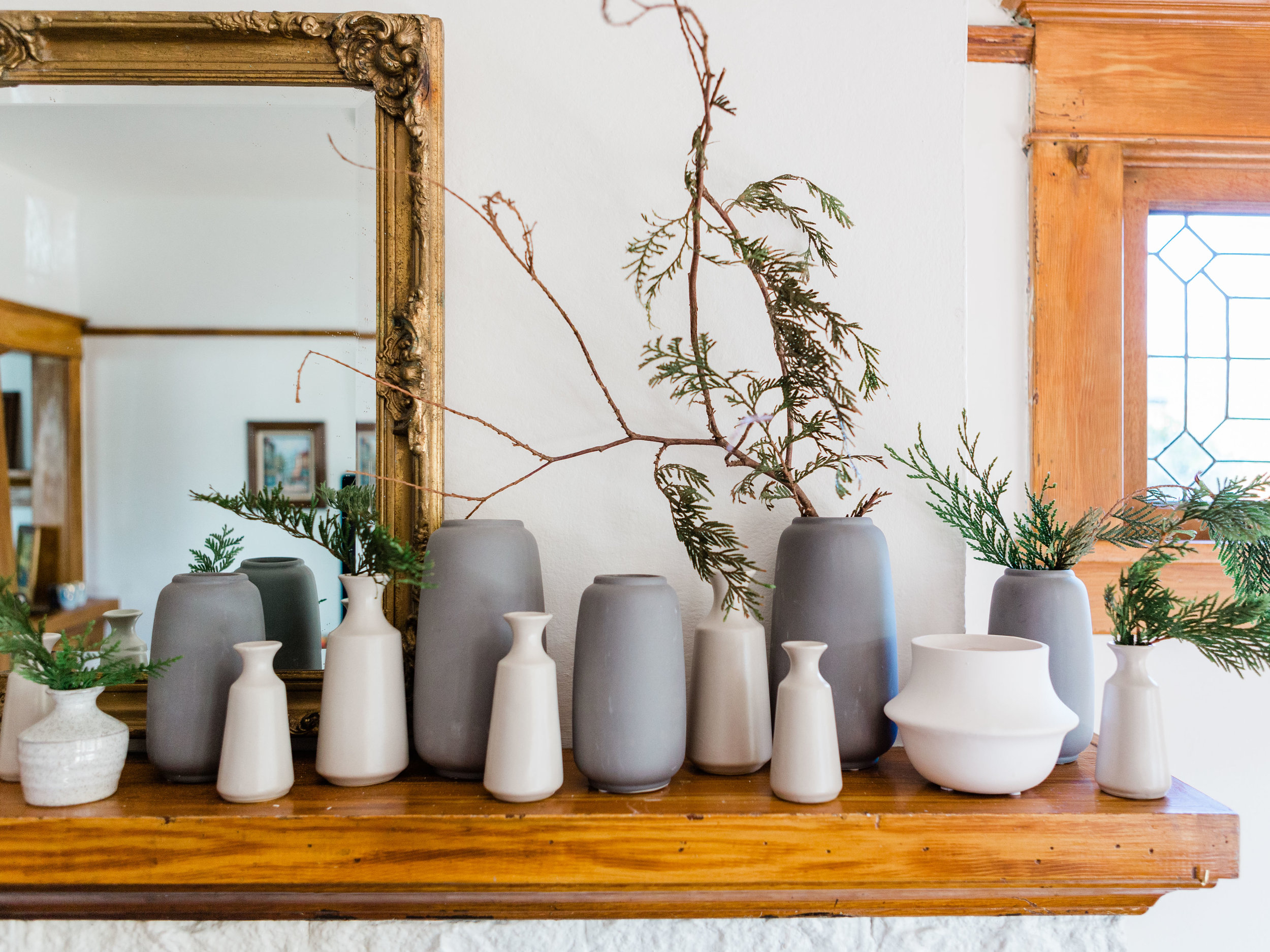 grey and white bud vases on mantle