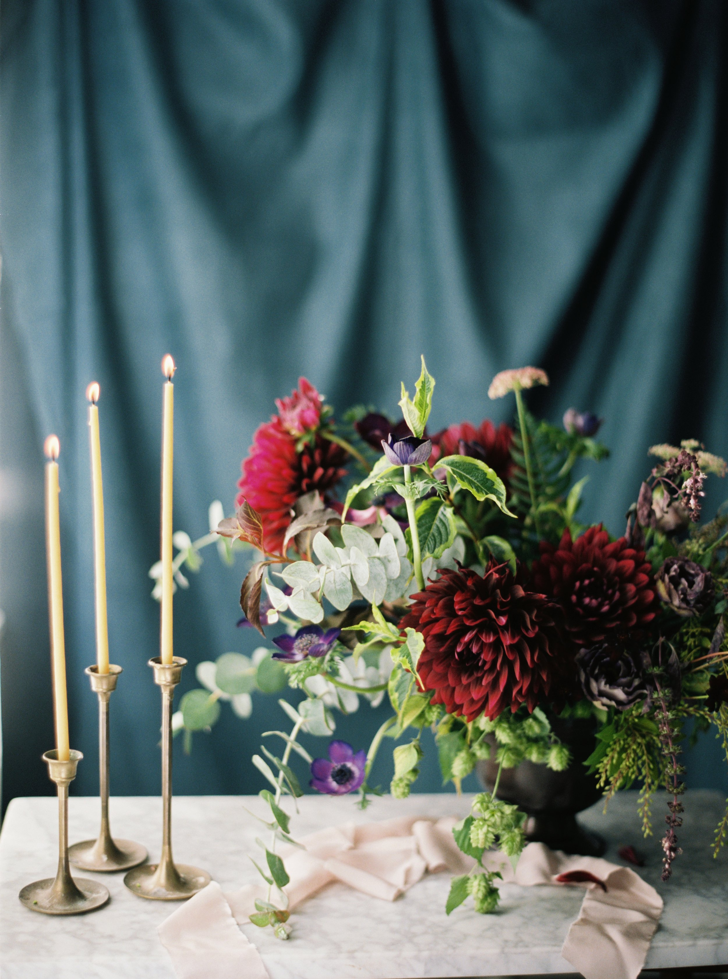 summer floral centerpiece featuring dinner plate burgundy dahlias and eucalyptus