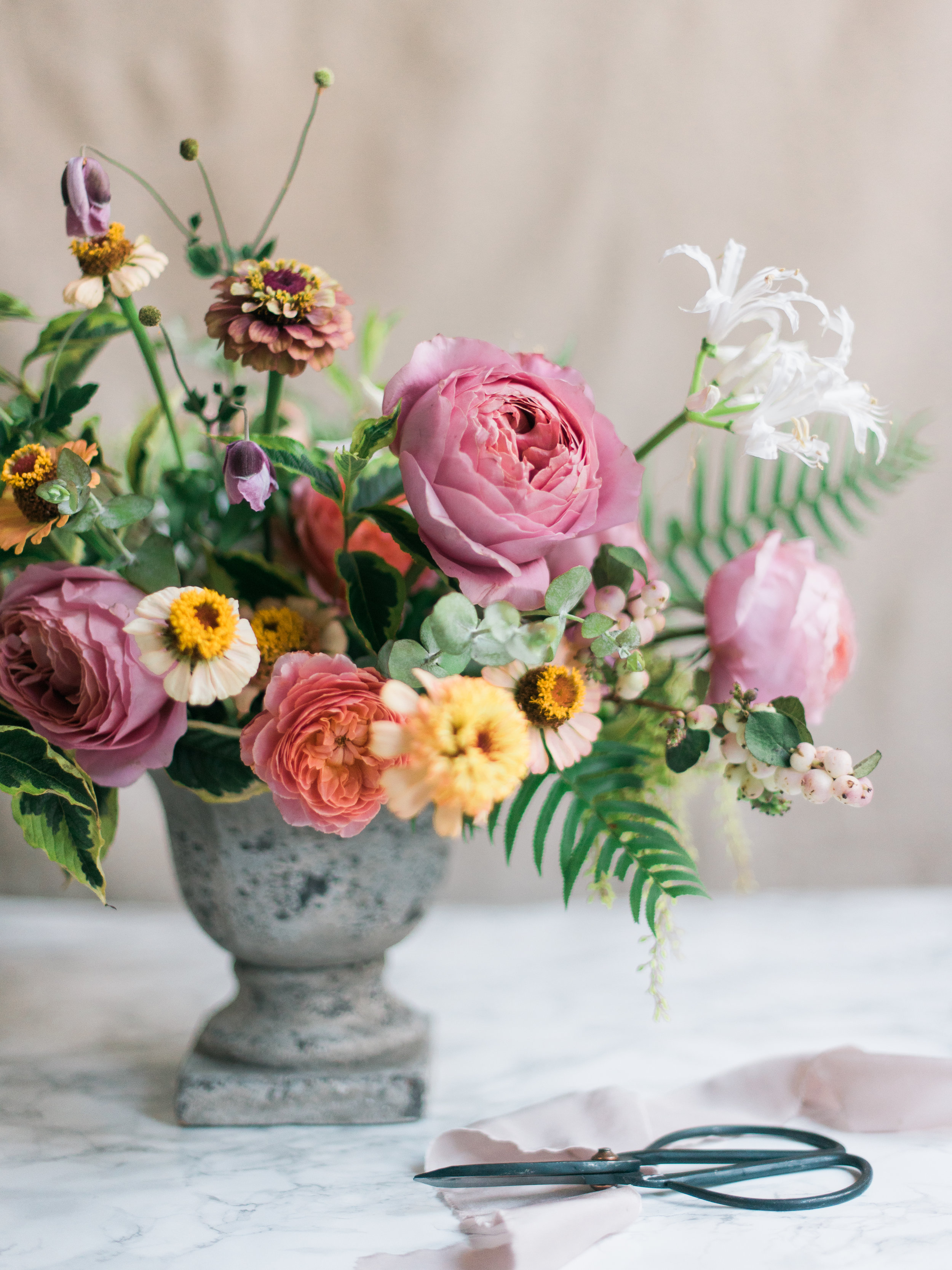 summer flower arrangement in shades of pink, yellow, peach and orange featuring zinnias, garden roses, ferns, and nerines