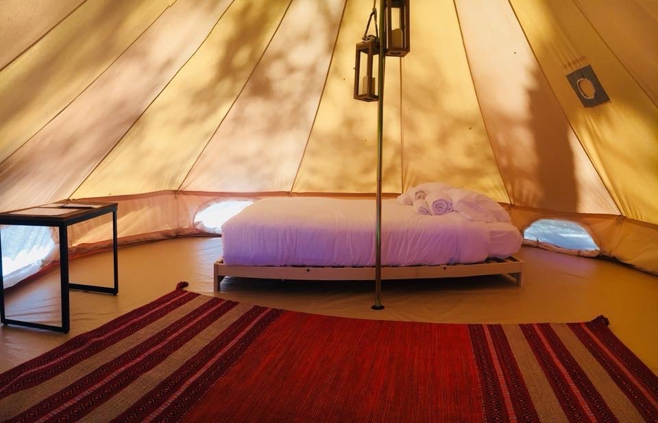Interior of glamping tent with queen bed, decorative rug, and lanterns
