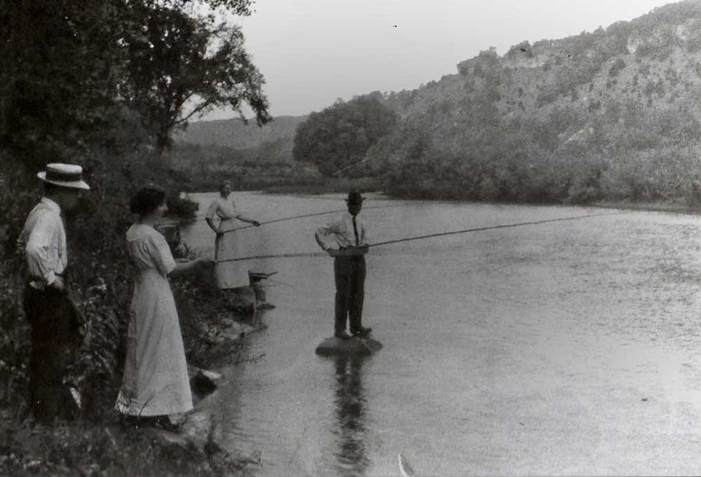 Adventurous women in dresses fishing with bamboo poles on the North Branch of the Root River.