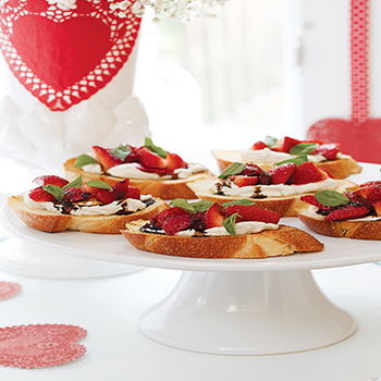 Nice Nibbles  Strawberry & Goat Cheese Bruschetta: In a small sauce- pan, bring 1⁄2 cup of balsamic vinegar to a simmer over medium low heat. Simmer for 8 minutes, or until reduced by half. Cool to room temperature. Heat a grill pan over high heat. Brush 12 slices ciabatta or other Italian bread with olive oil. Grill bread 3 minutes per side, or until browned. Spread grilled bread with goat cheese. Top with strawberries, add salt and pepper, and drizzle with balsamic syrup. Sprinkle with basil. Makes 12 servings.