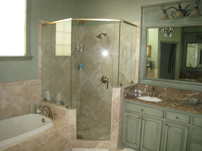 Bathroom Remodeling: From Traditional to Transitional If you currently use a traditional bathroom style and are thinking of making the switch to transitional, then there's good news for you. Making the 'transition' won't be hard at all. Transitional bathroom style is all about combining the best of both old and new. It's a great style for people who like to experiment with different looks, as it is a place where traditional and contemporary design elements meet. Utilizing the simplicity and clean style of contemporary bathrooms and pairing them with the functionality of a traditional bathroom is typical of the transitional style. Transitional bathrooms will often be very understated, with a classic feel. Materials and furniture Counters and flooring are often made from granite, slate or marble, giving the room a natural feeling, while still being cold and clean. The surfaces are easy to maintain and hard to damage – they will last the test of time while still appealing to the modern taste. Bathtubs are often left out of transitional bathroom design, in favour of a stylish shower unit with curved glass, tiled walls and multiple showerheads. Modern 'mid-century' cabinets and vanities make a great addition and can be paired with natural elements such as wooden benches and stone floor to further bring together the traditional and contemporary styles. Shapes and colors Typically, a transitional bathroom will use a lot of round edges, soft shapes and subtle curves. Consider this when choosing faucets, towel racks and other furniture, including the shower doors. Ideally, your traditional cabinets and vanities would share the same curvature as the modern shower unit – their shape being the uniting factor that holds the design together. The final consideration is color, which is soft and muted in a transitional design. Tones of whites, greys, tans, light blues and beiges are all used to create an atmosphere of elegance, beauty and functionality. Simple colors are also very e