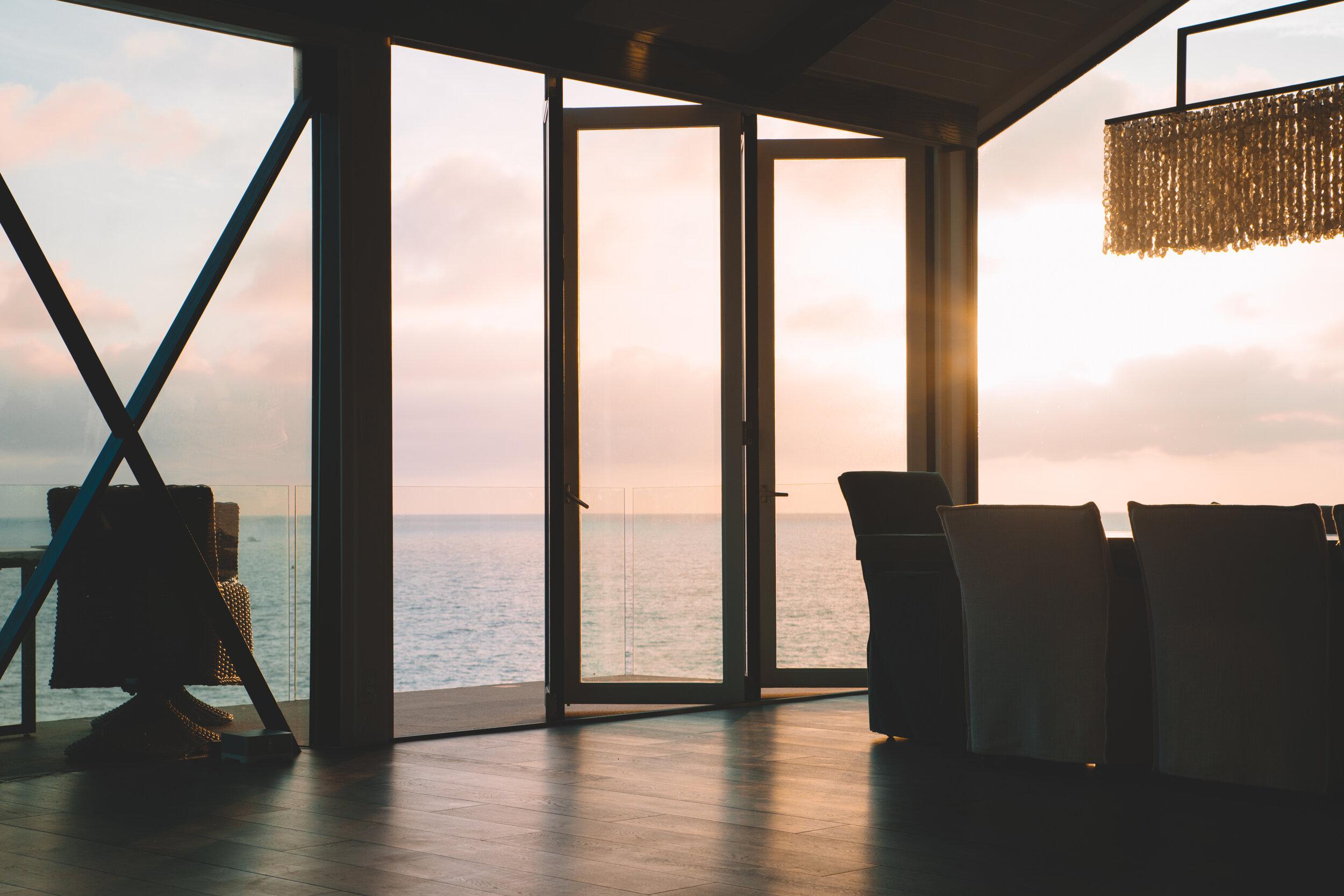 Floor to ceiling windows and glass door tinted overlooking ocean.