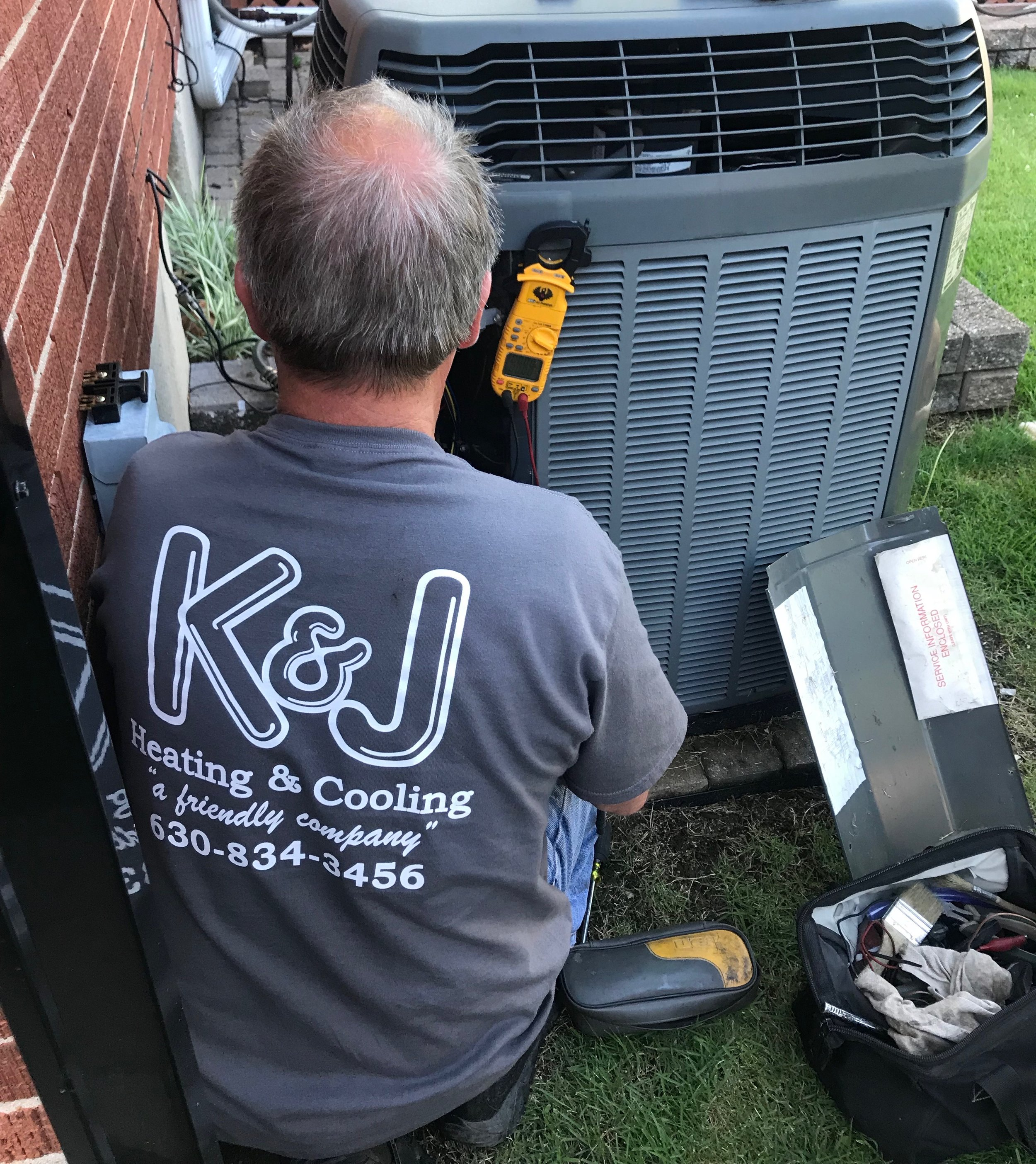 Trusted K & J Heating and Cooling, Inc. HVAC Service Technician Repairing a Customers Air Conditioner.