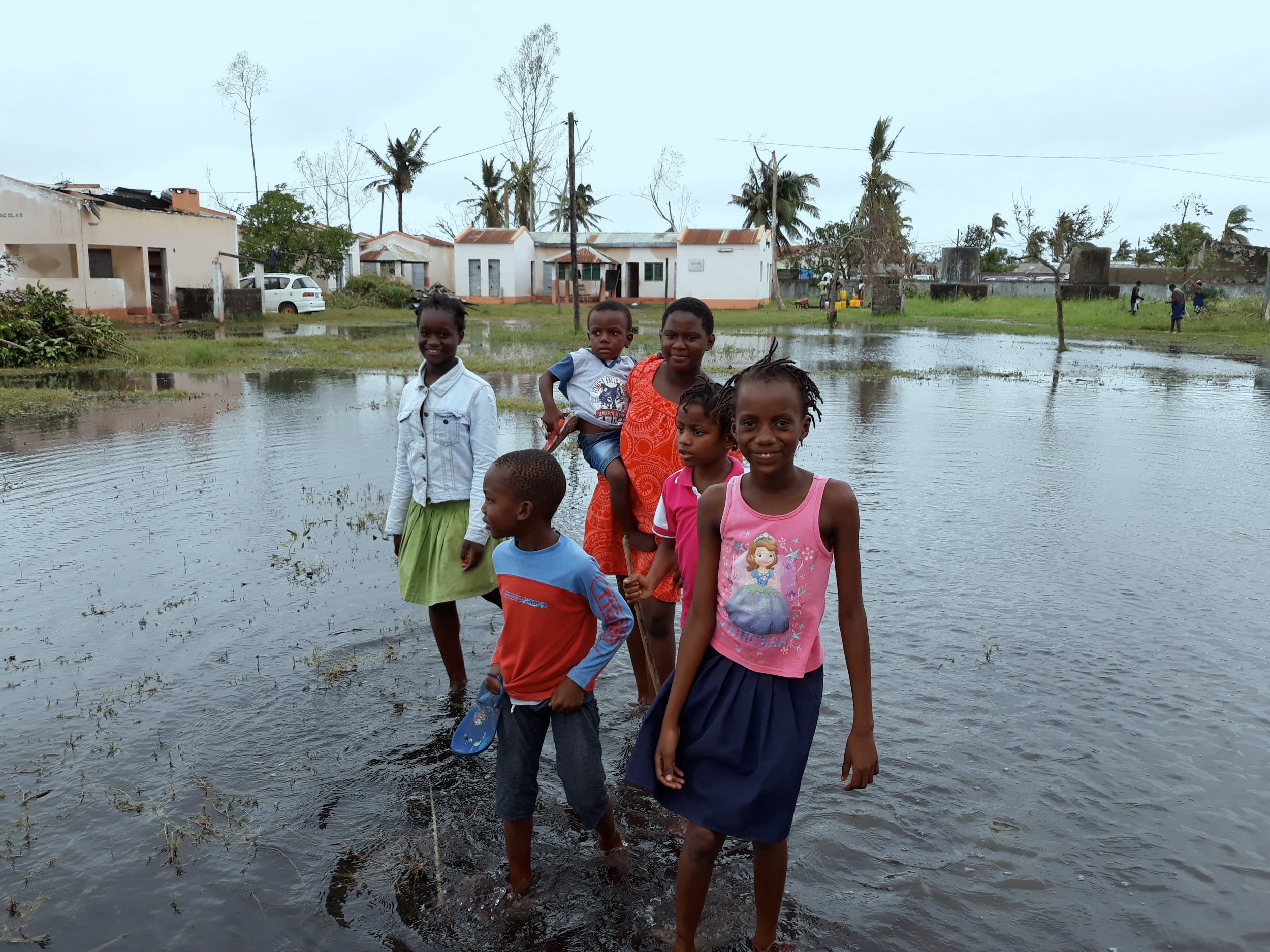 Children from one of ASEM's schools wade through the waters after Cyclone Idai, in Beira, Mozambique.