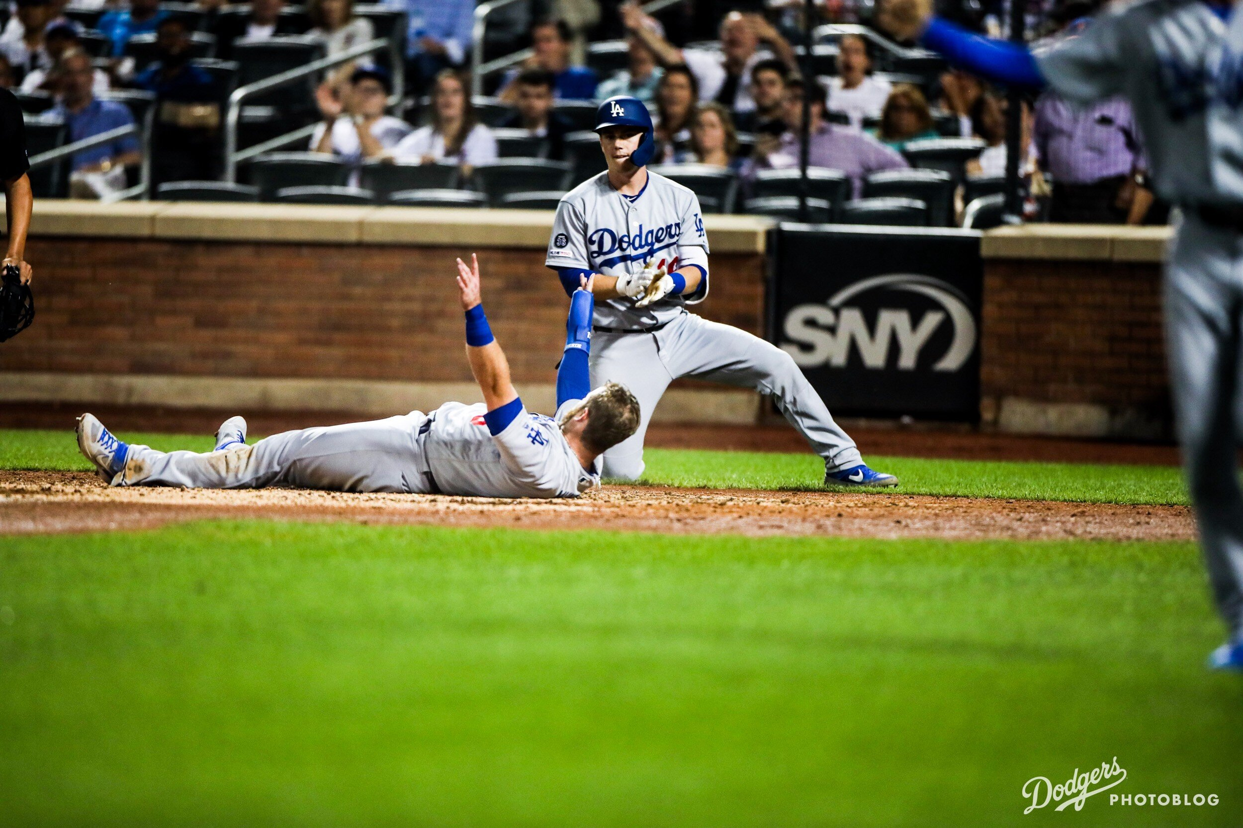 Max Muncy laying on the ground after scoring a run. Lucas Stevenson/MLB.com