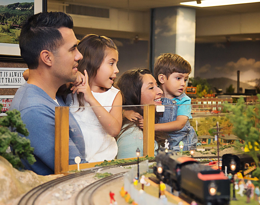 family-of-four-looking-at-model-trains