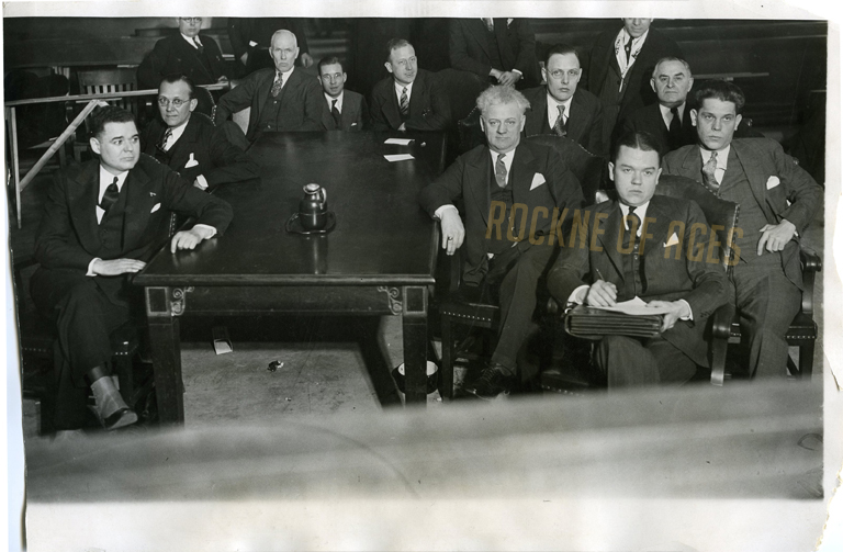 Al Capone hitman Leo Brothers, (far right), surrounded by prosecutors and attorneys on his defense team on March 16, 1931, the opening day of the Jake Lingle murder trial in Chicago. A jury convicted Brothers of murdering the Chicago Tribune reporter in a downtown Chicago subway station… CREDIT: ACME Photo