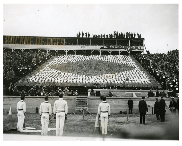 "Navy buglers atop the stadium roof in Baltimore blowing taps in memory of the fallen Notre Dame coach while Middies in the stands spell out the name ""Knute Rockne"" during the Notre Dame-Navy game on Nov. 14, 1931… CREDIT: ACME Photo"