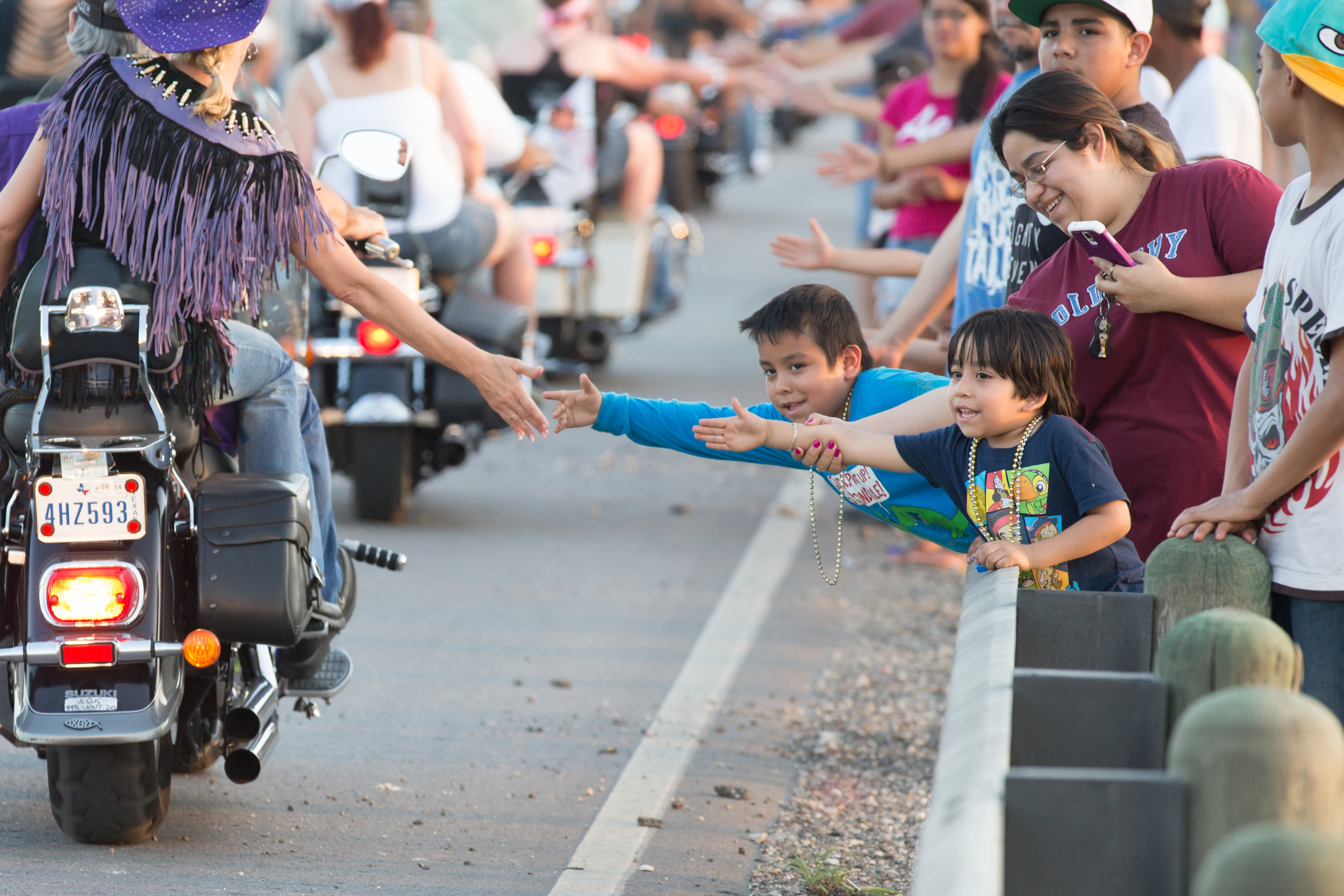 An onlooker high fives riders taking part in the Austin Republic of Texas Bike Rally.