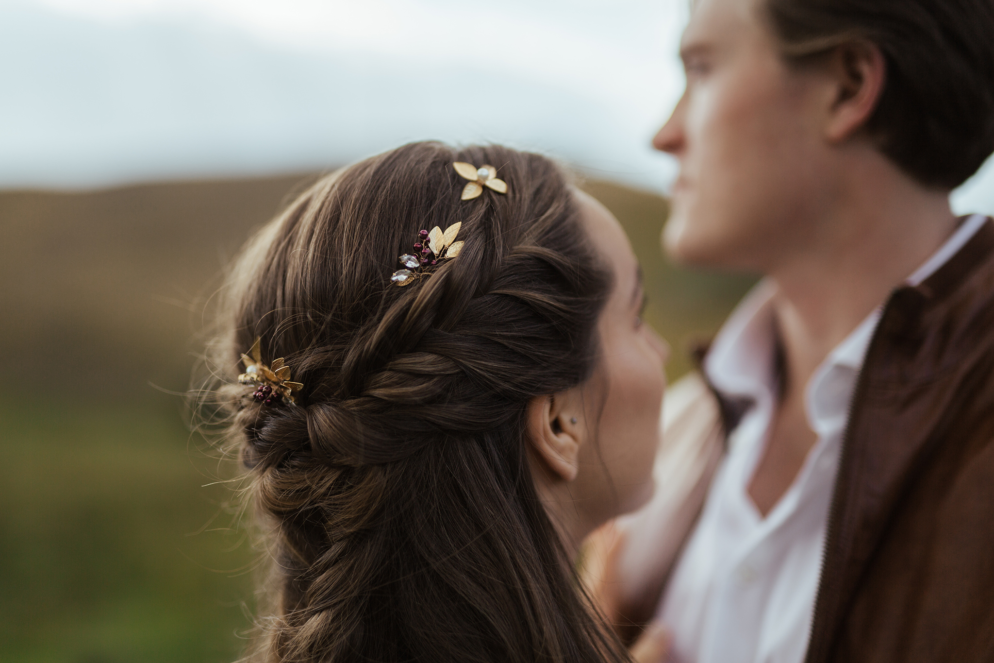 The bride's hair was gently braided back into a stunning fishtail, and the   Davie and Chiyo   gold leaf pins added the prettiest touch to the elegant 'do.