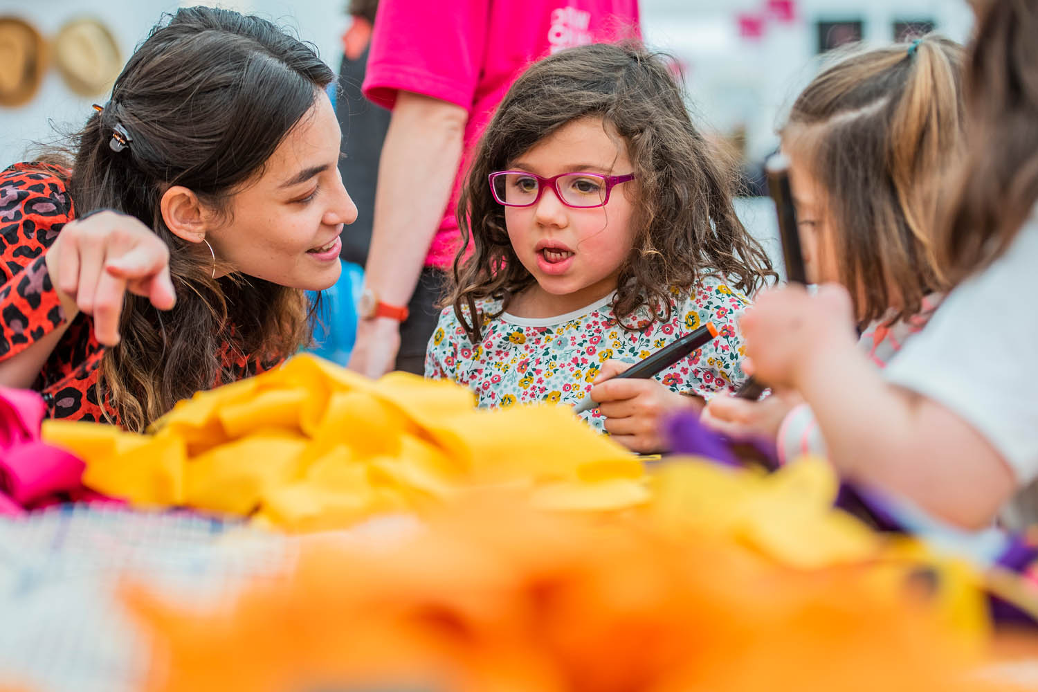 Sophia talking to a young brunette girl with red glasses. She is pointing to yellow material