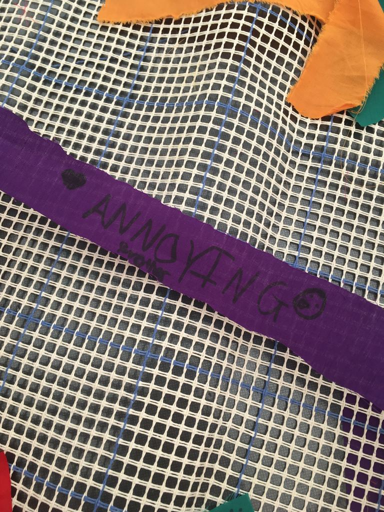 A purple strip of material which says 'we both have annoying siblings' on it