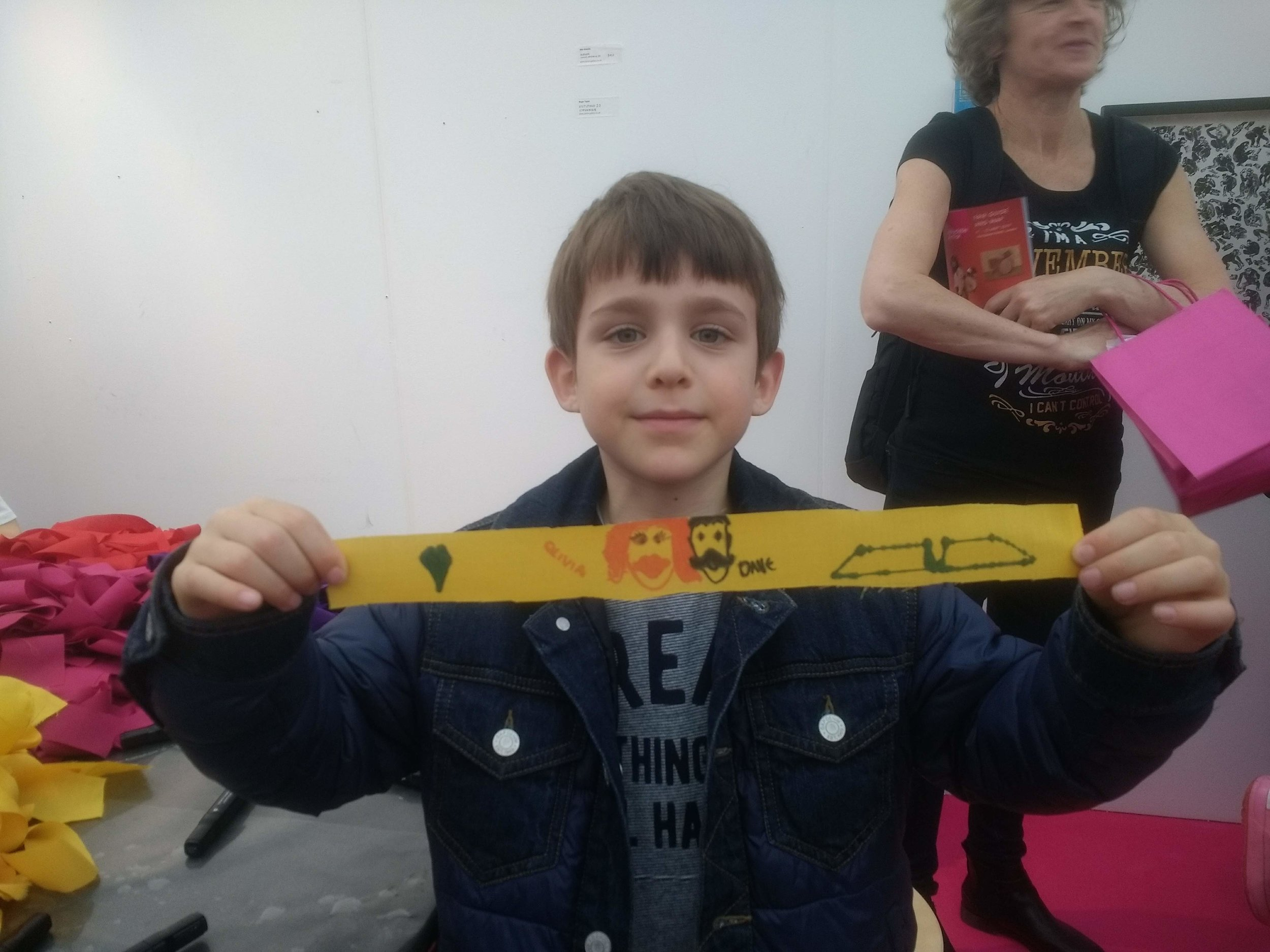 A little boy holding up a yellow strip with drawings of faces on it