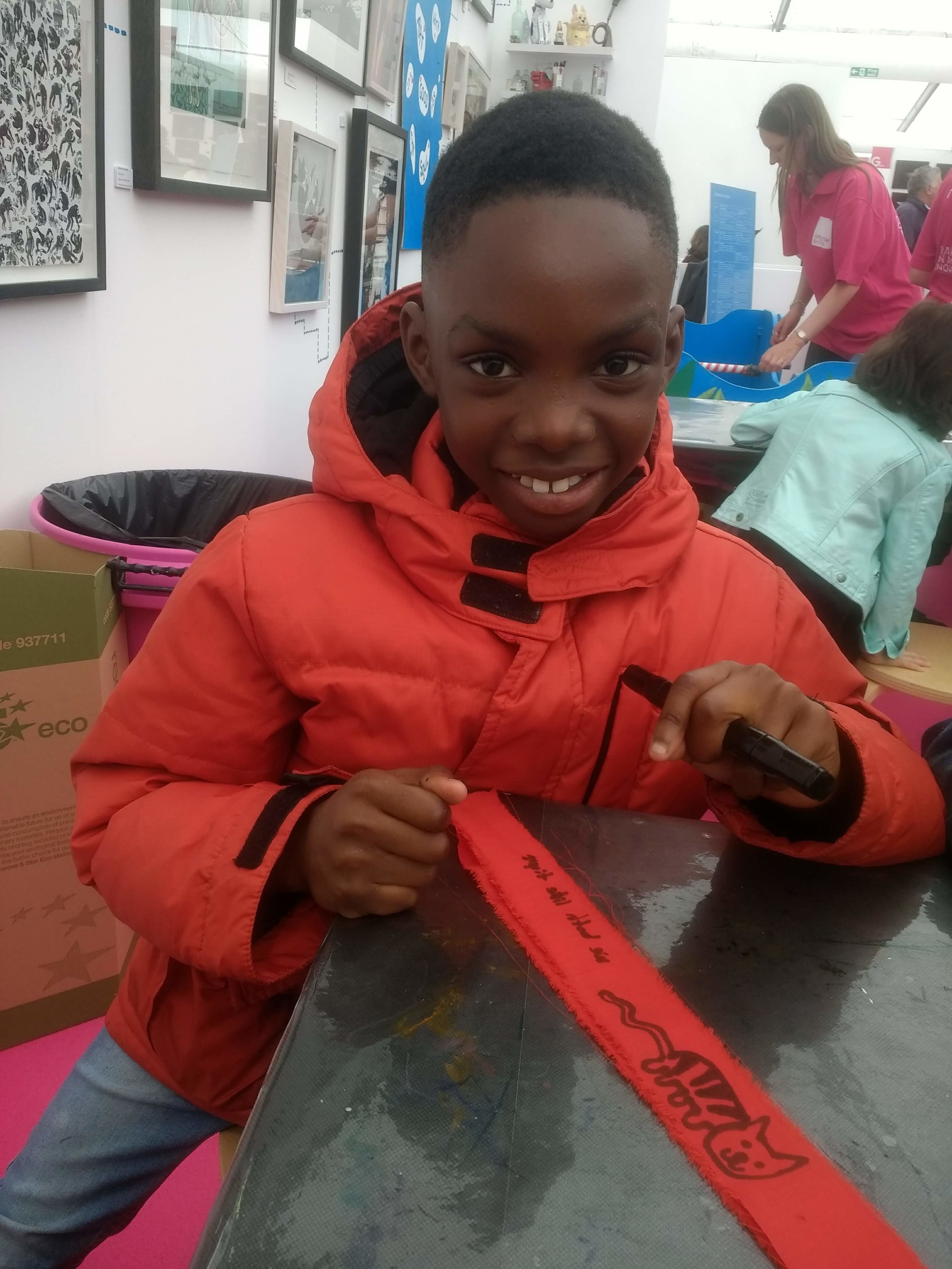 A little boy smiling and pointing to his red cloth