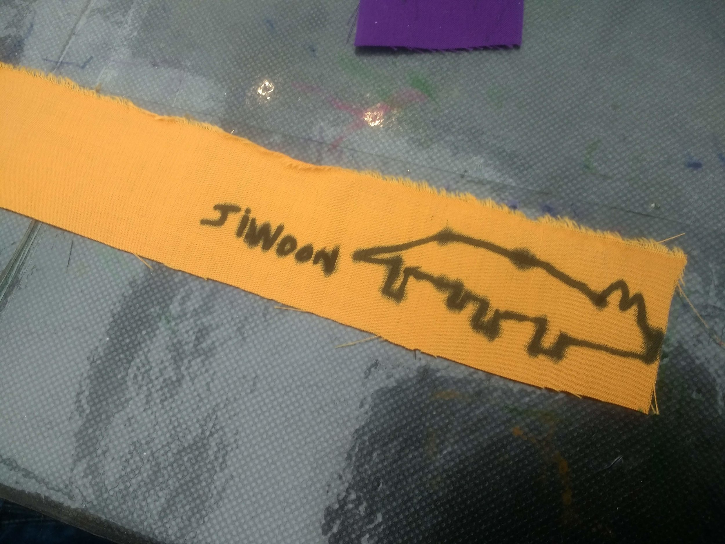 A yellow strip of material which says 'Jiwoon' on it
