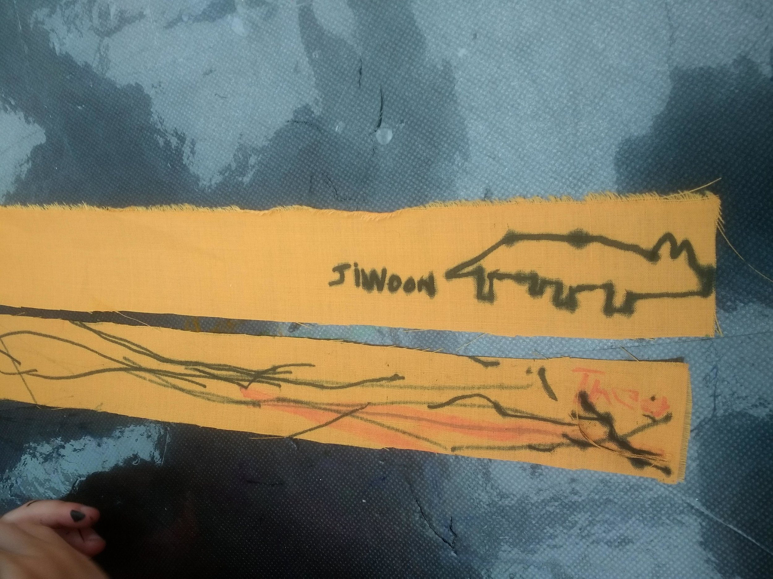 Two strips of yellow material drawn by the children