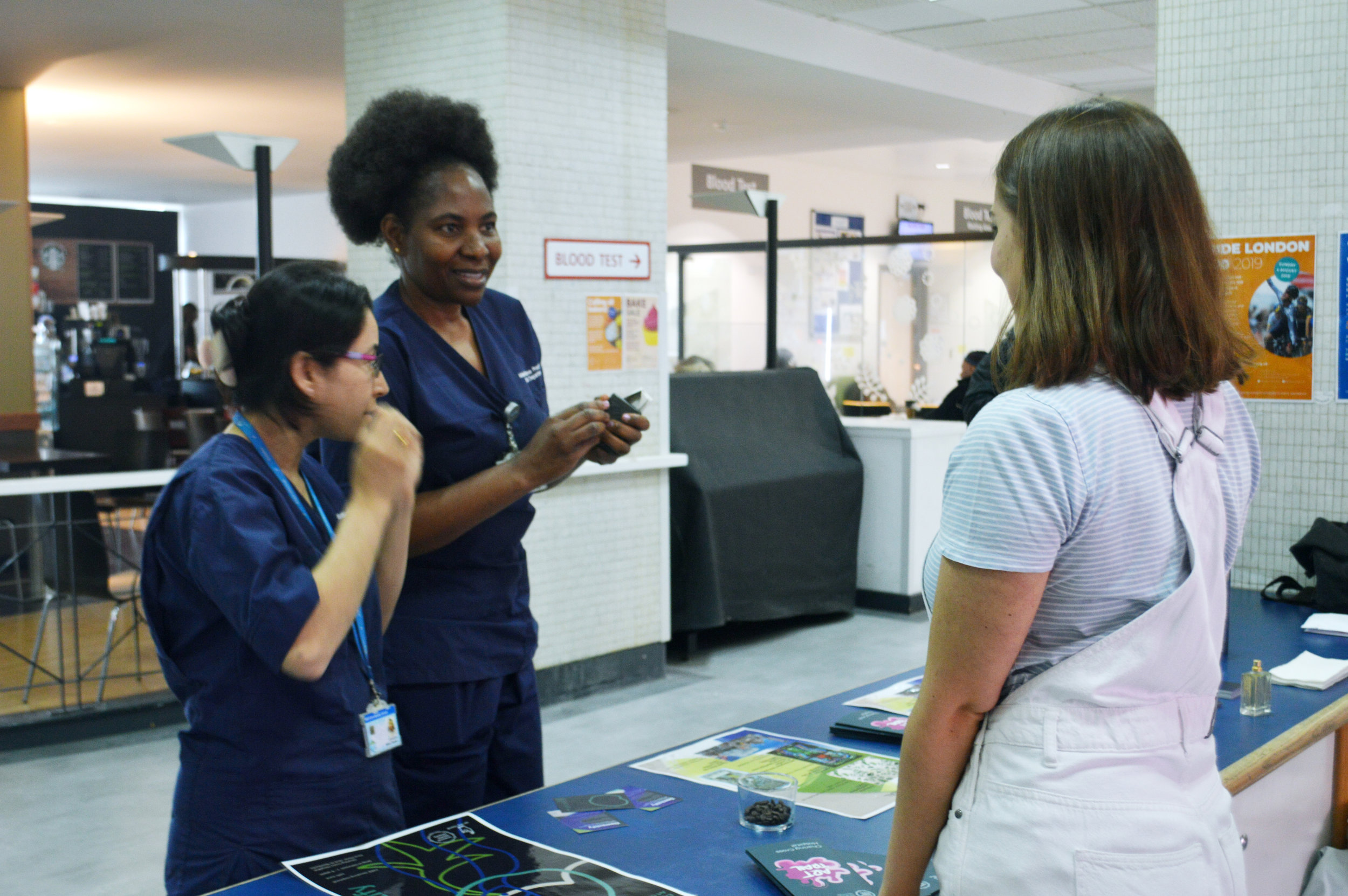 Mathilda speaking to two nurses about the project