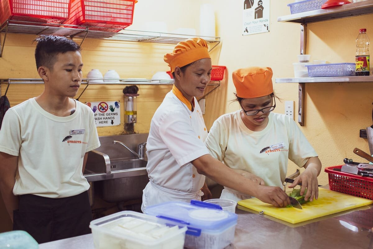 Two students being taught how to cut vegetables in the streets kitchens. The chefs are wearing orange hats