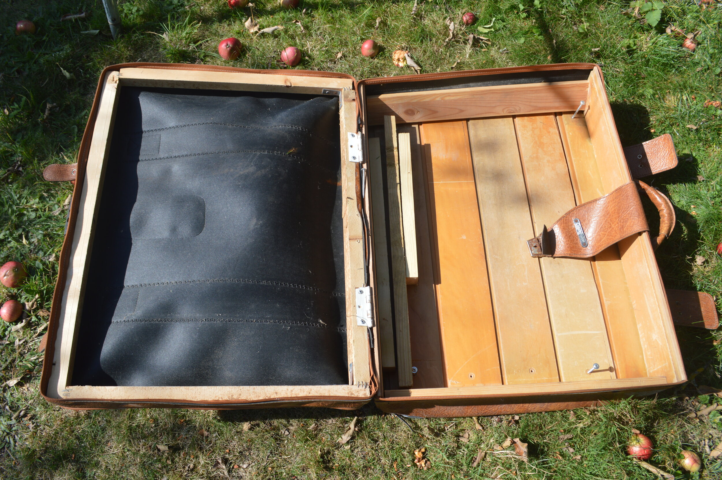 Leather case open on grass with wooden frame