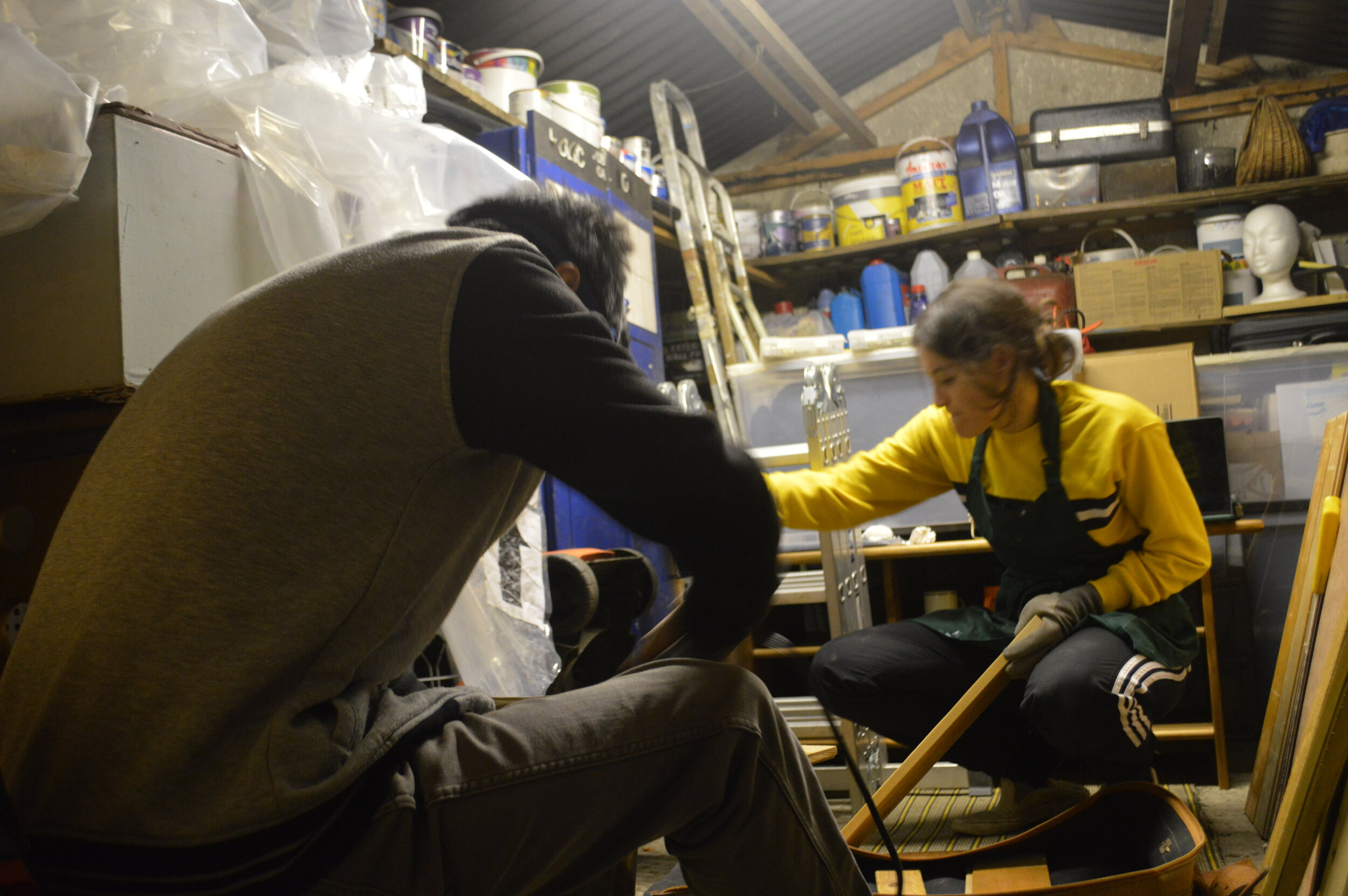 Sophia and Minh in the shed working on the wooden frame. Minhs back is to the camera