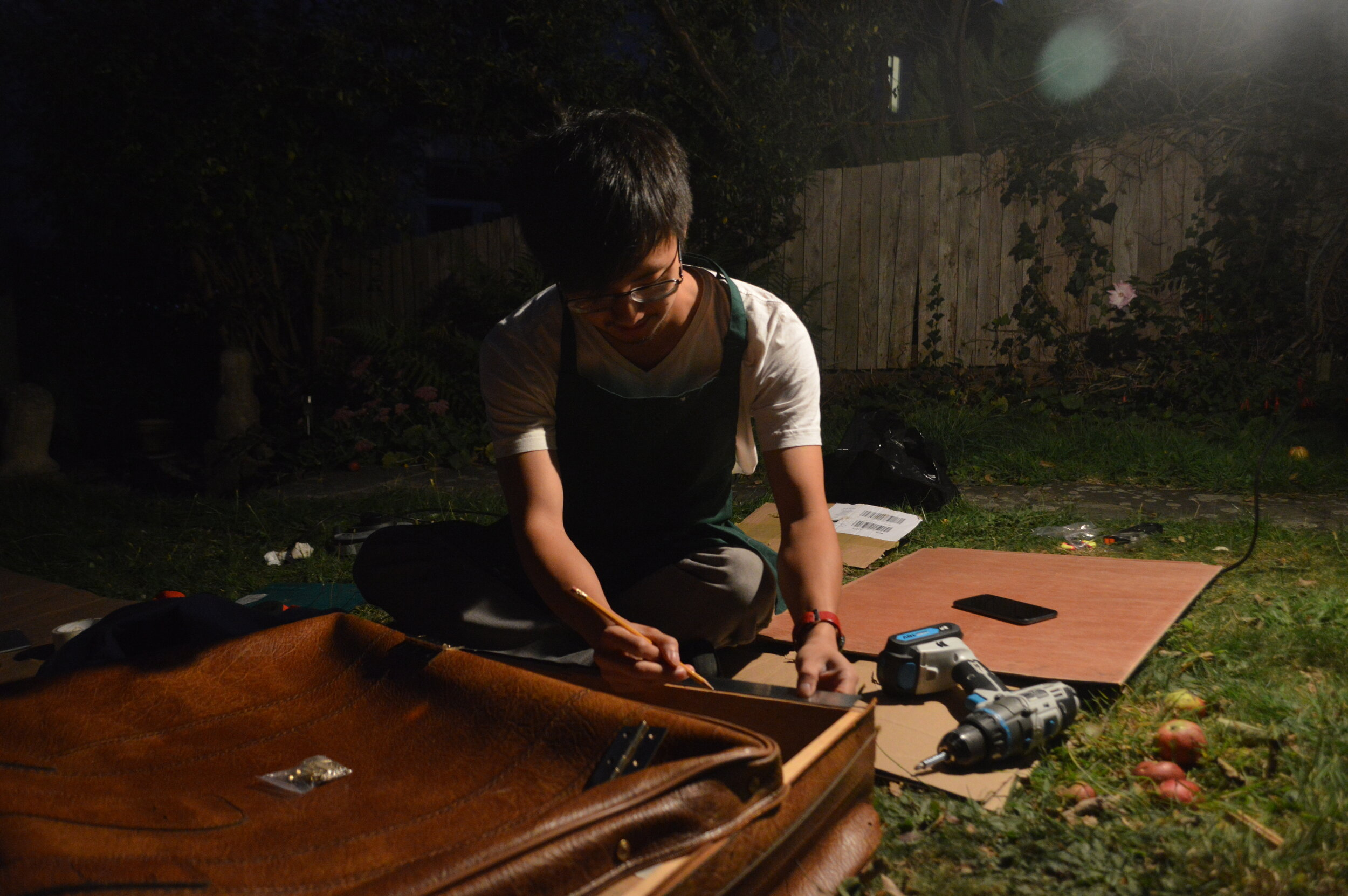 Minh sitting down outside nailing wood into the leather suitcase