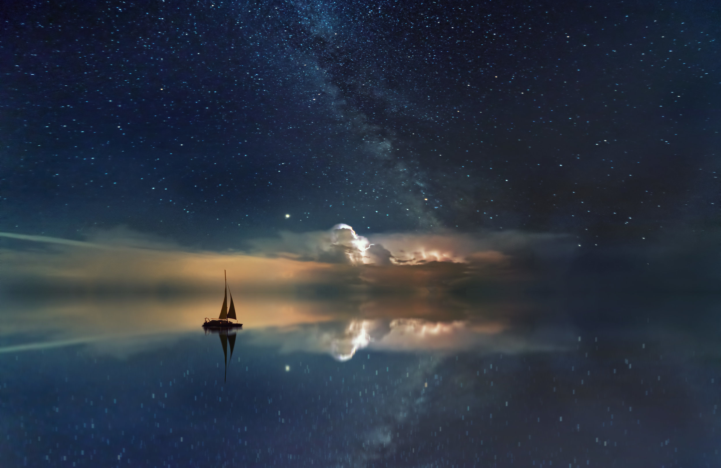 [Photo ID: A photo of an evening starry sky, a sail boat is floating in the water towards the peach clouds]