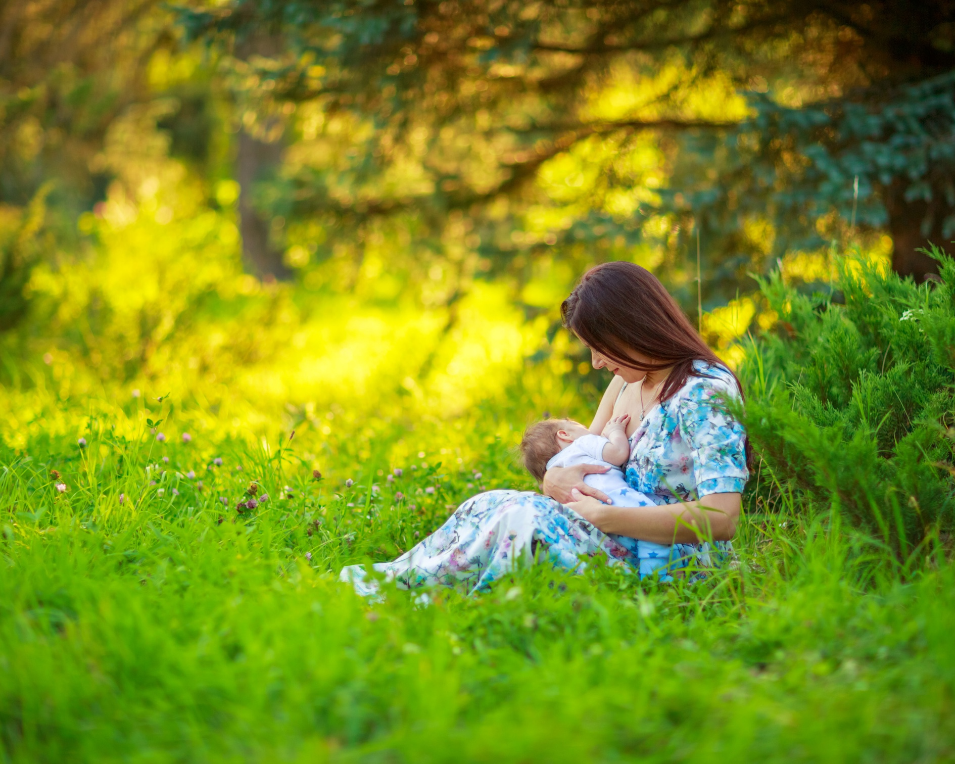 Image of woman in green grass with forest behind her in a floral dress nursing a baby.