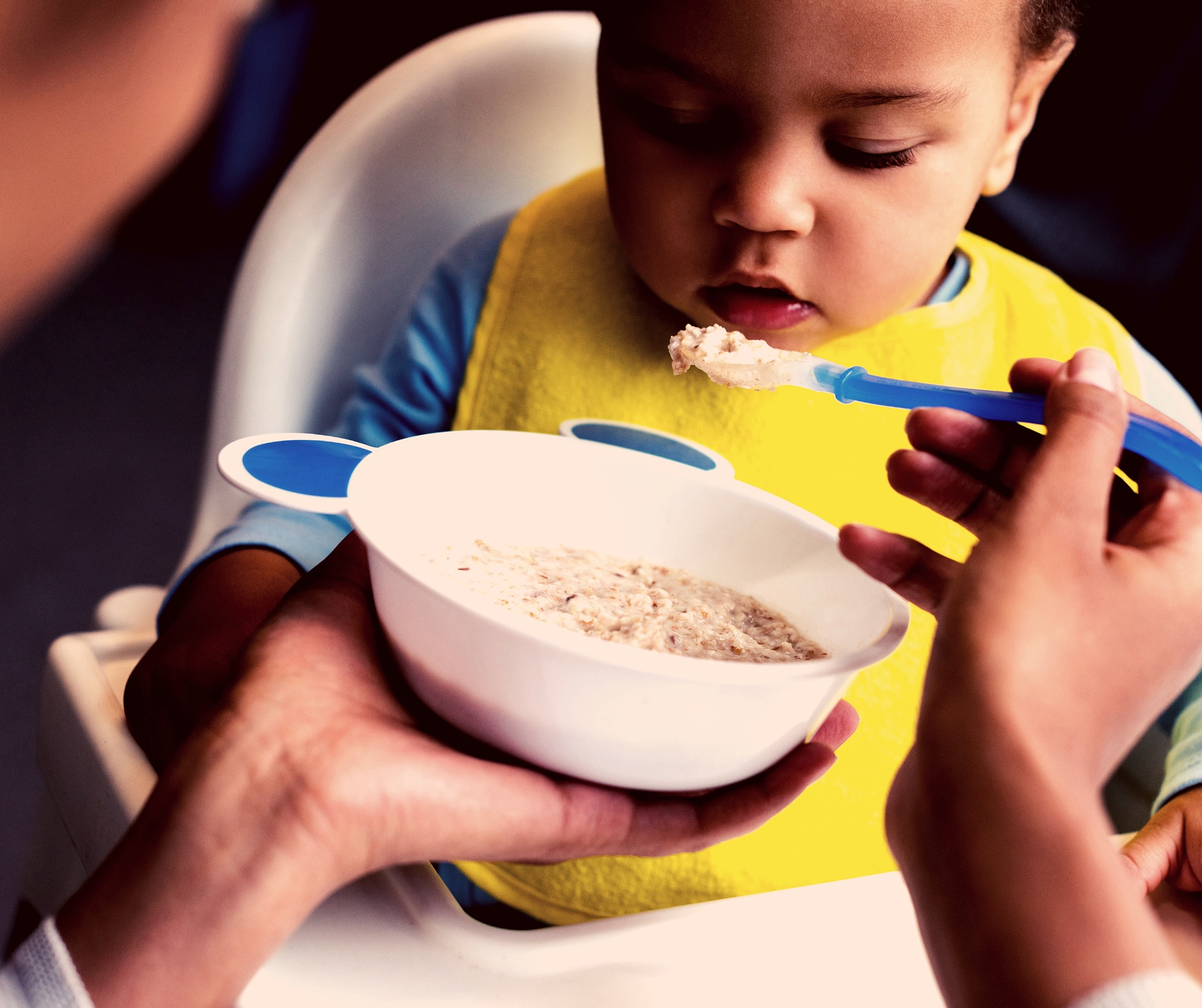 Photo of baby being spoon fed by female caregiver out of a bowl