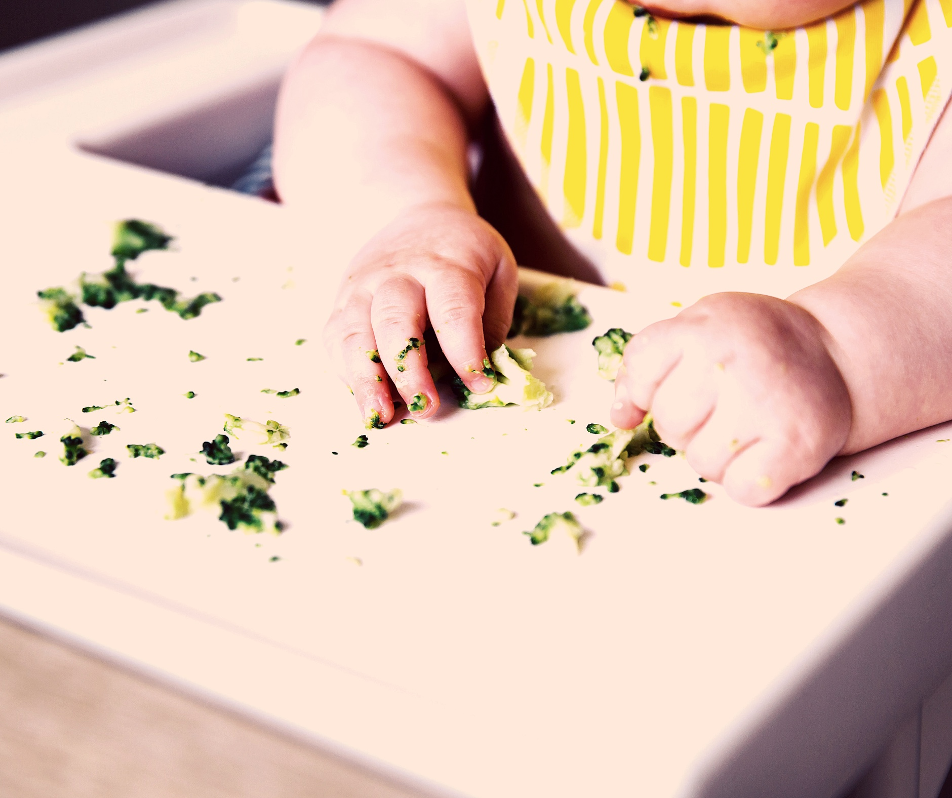 White chubby baby with bright yellow bib playing with cut up veggies on a high chair tray.