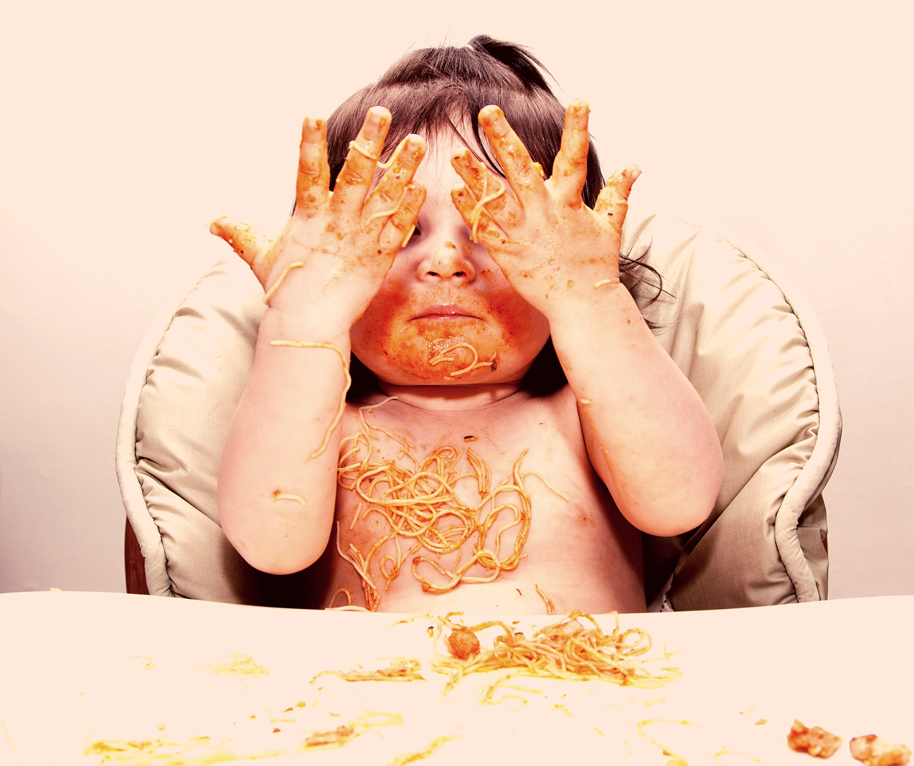 White dark hair Baby eating spaghetti with very messy tray and face.