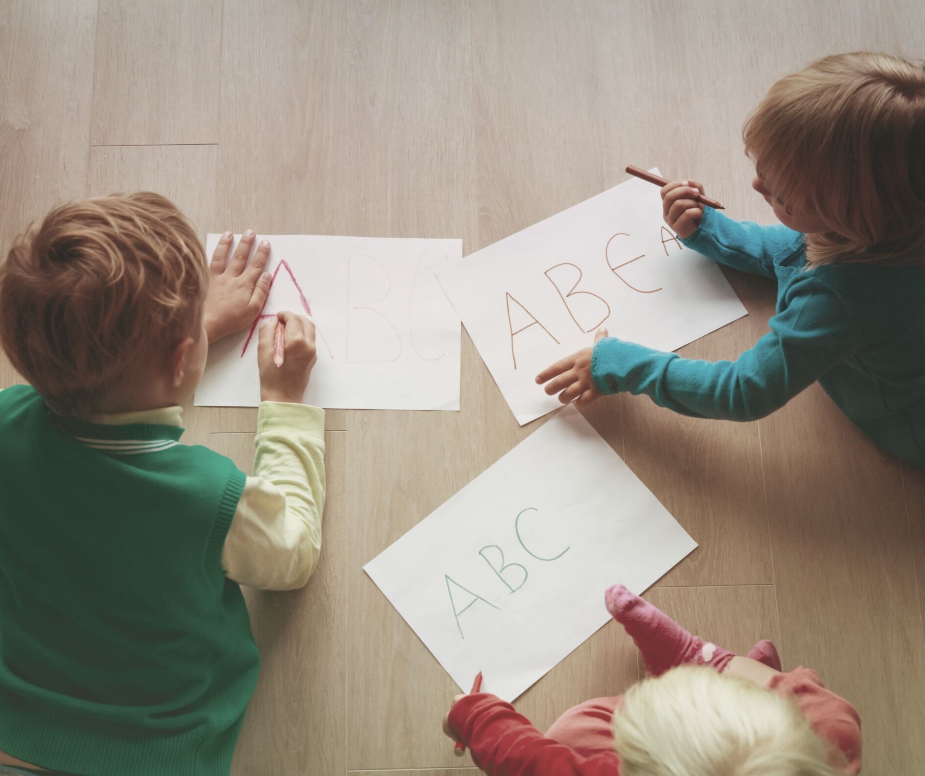 Children practicing their ABCs on the floor